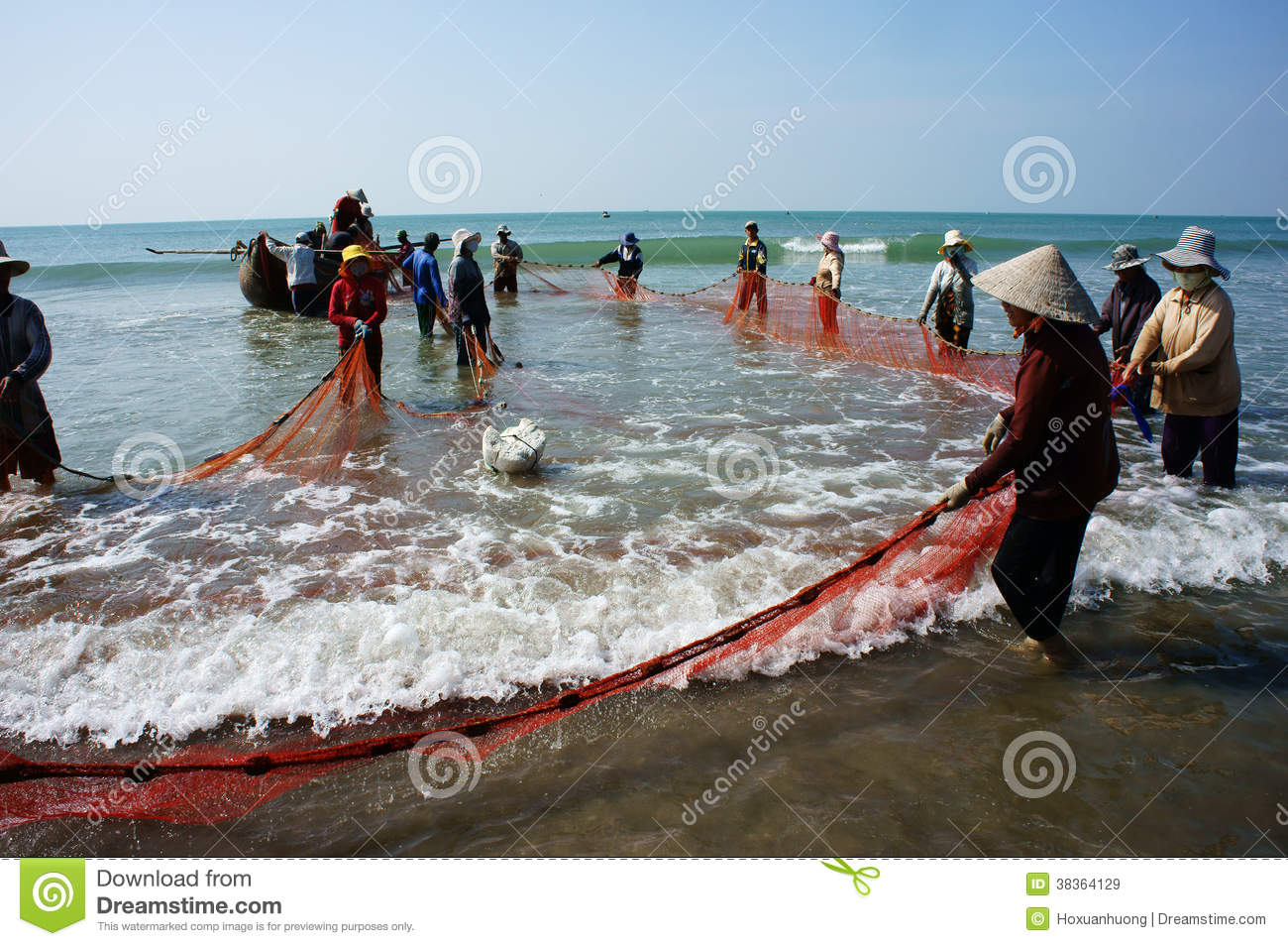 Team work of fisherman on beach editorial stock image for People catching fish