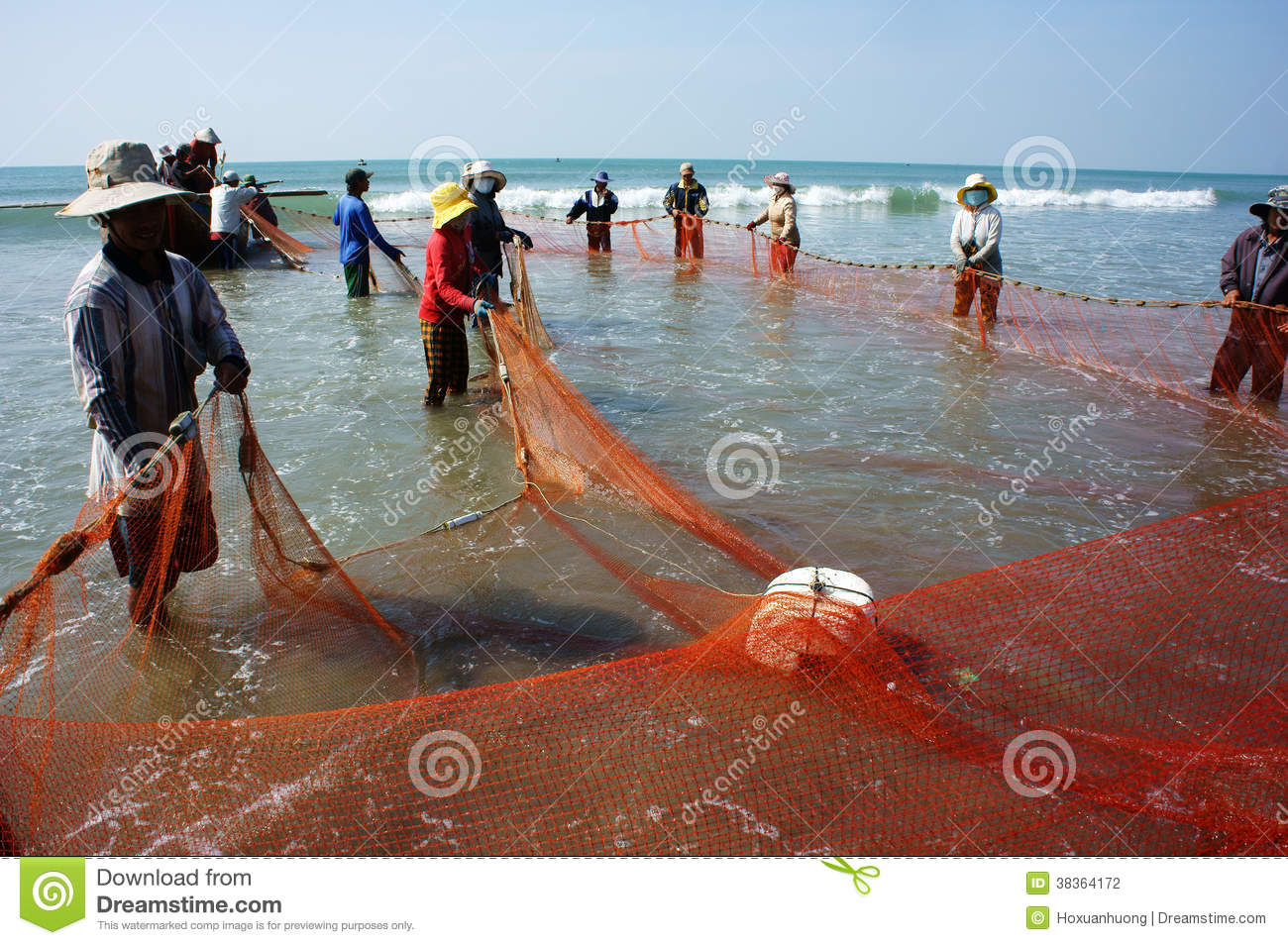 Team work of fisherman on beach editorial photography for People catching fish