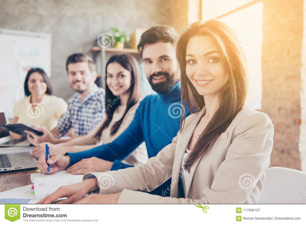 Teambuilding concept. Close up focused photo of five cheerful successful entrepreneurs, sitting and smiling at the conference, dr