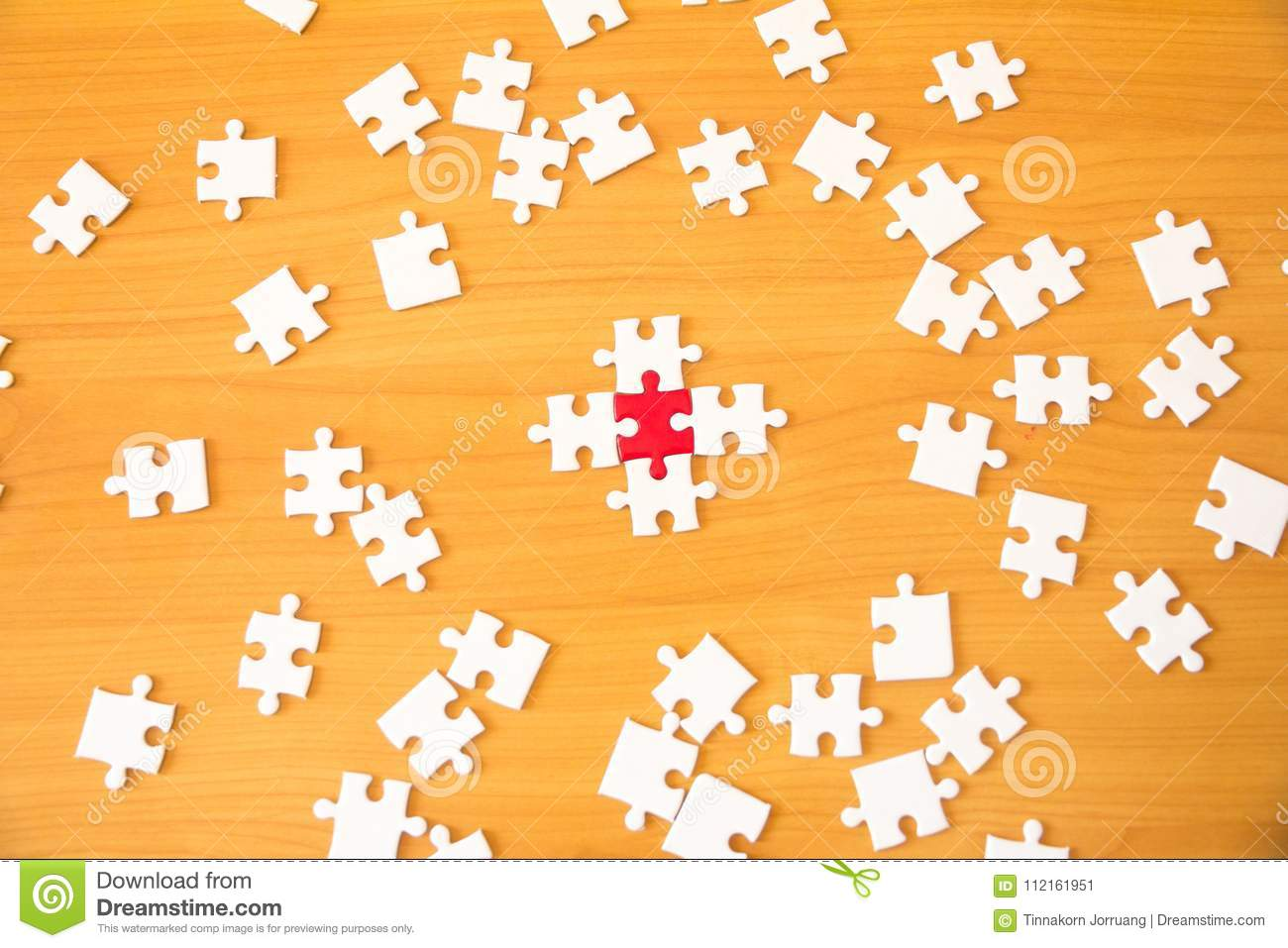 Teamwork concept using white and red puzzle pieces being fitted