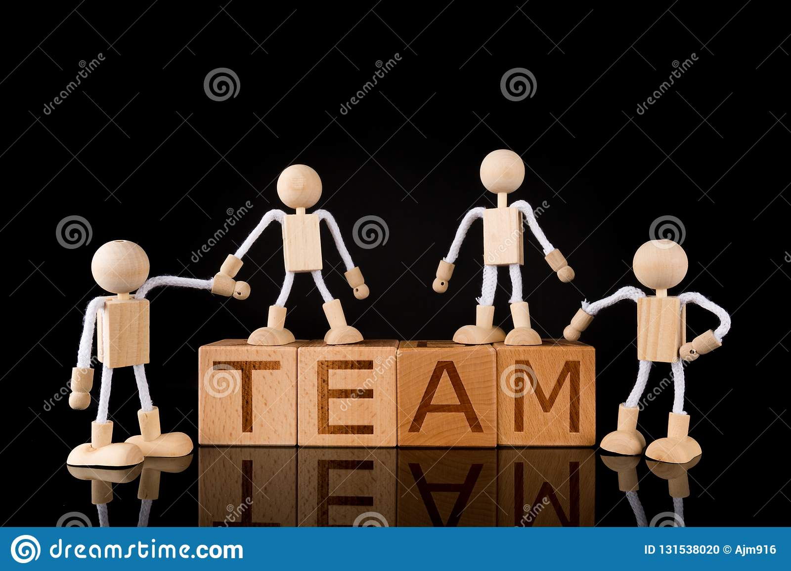 "Teamwork concept, Wood cube block with word ""TEAM"" and Wooden Stick Figures team."