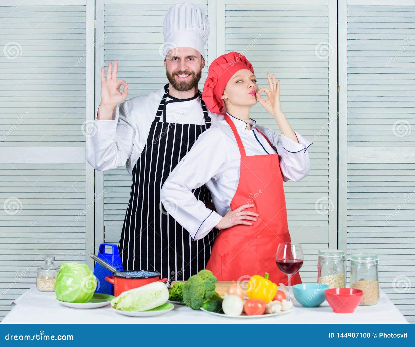 Teamwork i k?k Koppla ihop matlagningmatst?llen Kulinariska partners f?r kvinna och f?r sk?ggig man L?cker familjmatst?lle anledn