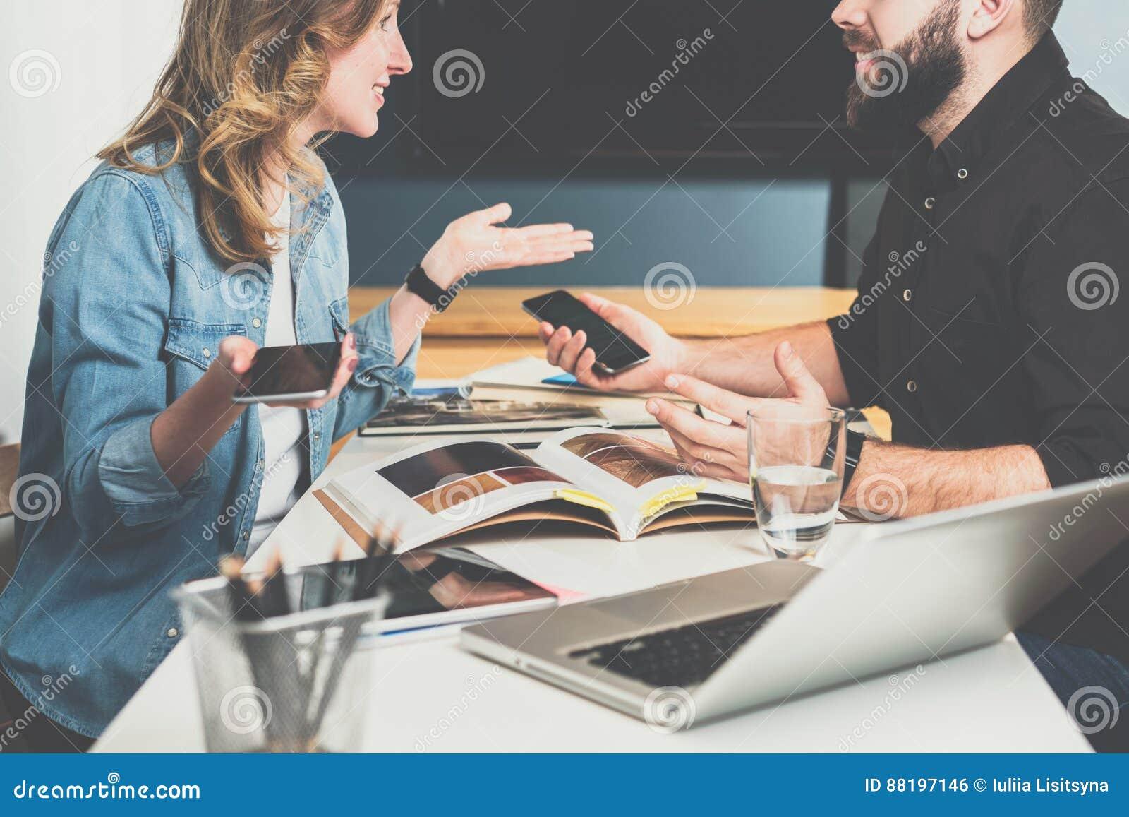 Teamwork, junge Designer sitzen bei Tisch im Büro und wählen oben Fertigungsmaterialien im Katalog aus Lächelnder Geschäftsmann u