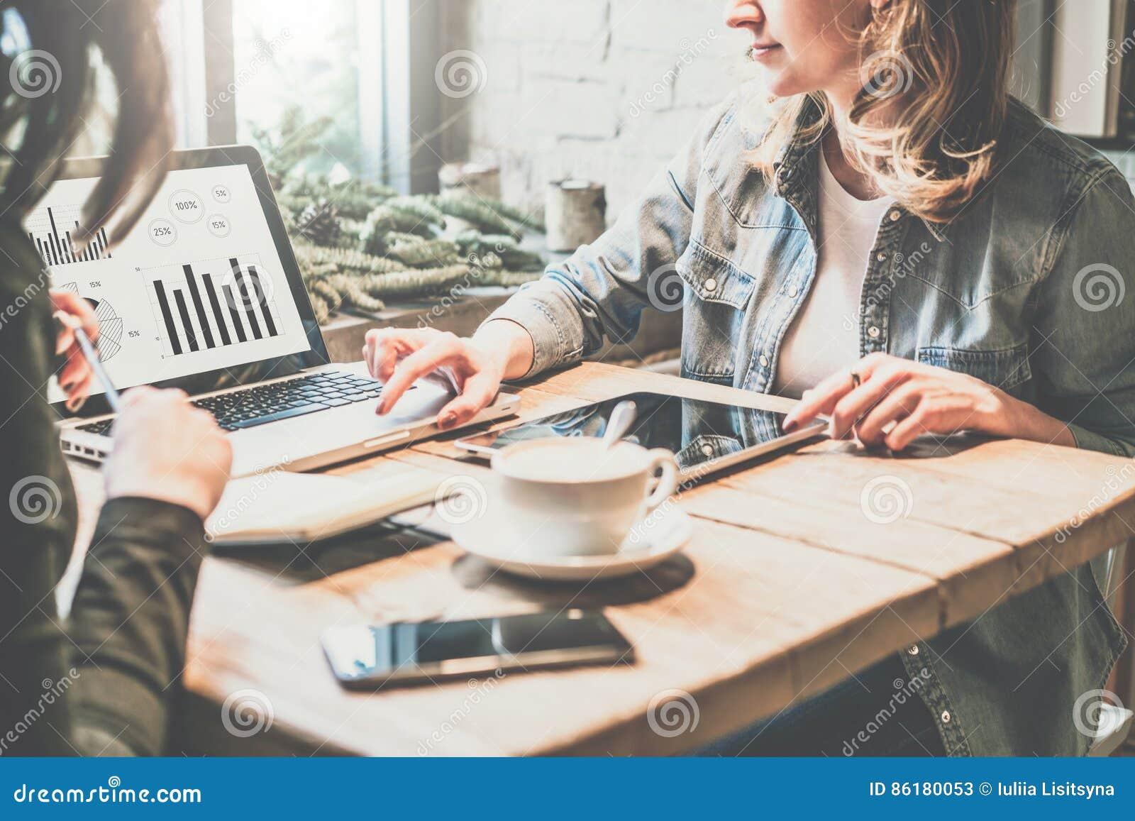 Teamwork A mulher de negócio de dois jovens que senta-se na tabela na cafetaria, olhar na carta na tela do portátil e desenvolve
