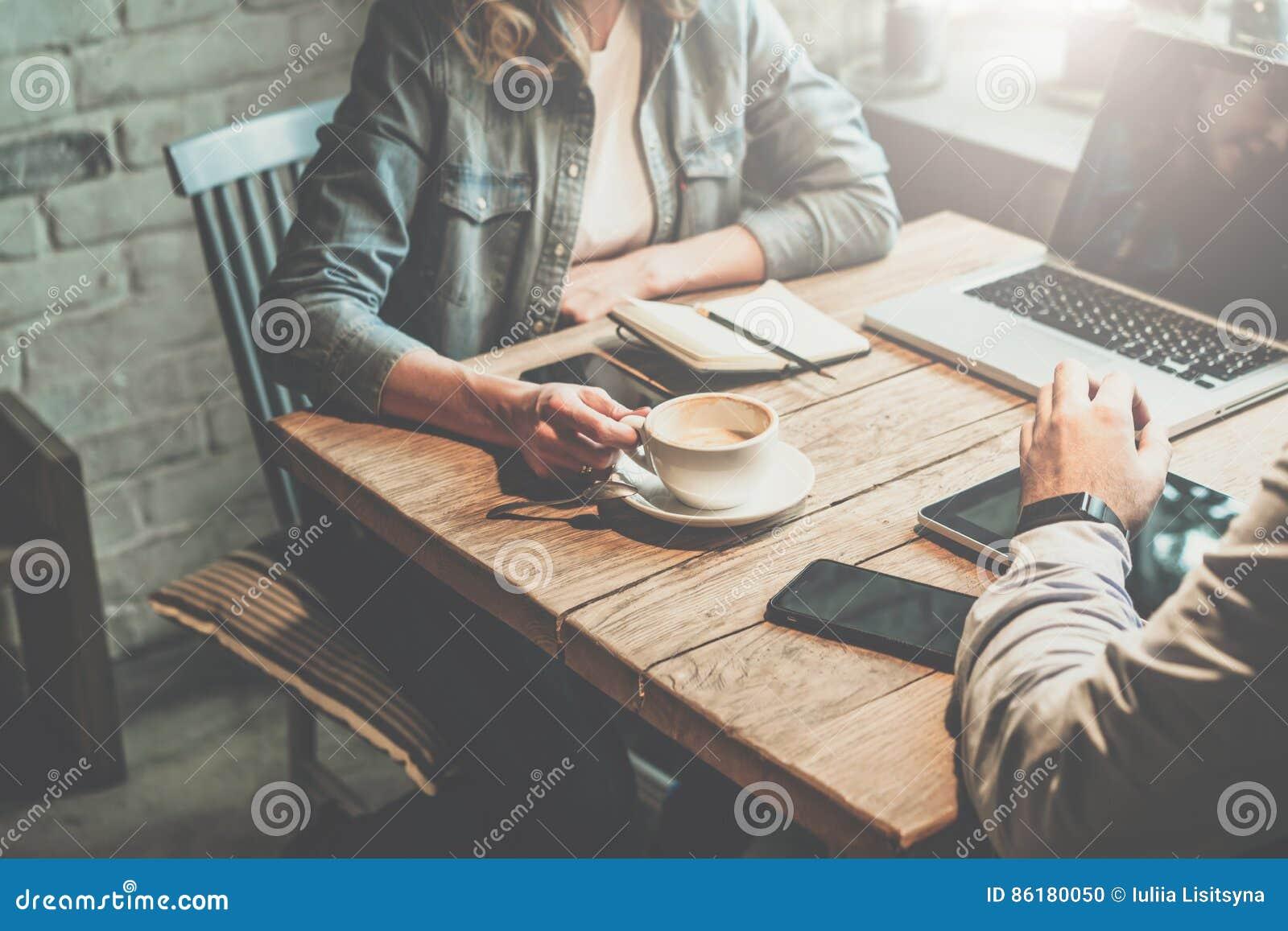 Teamwork O homem de negócios e a mulher de negócios que sentam-se na tabela na cafetaria e discutem o plano de negócios