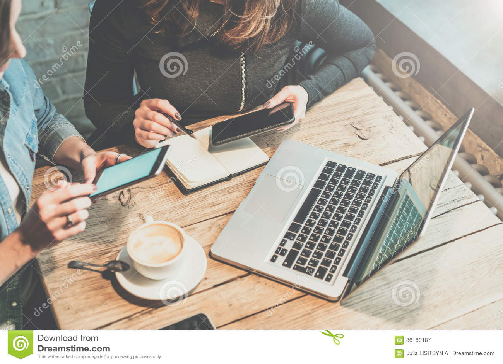 Teamwork Två unga affärskvinnor som sitter på tabellen i coffee shop, blick på din smartphoneskärm och, diskuterar affärsstrategi