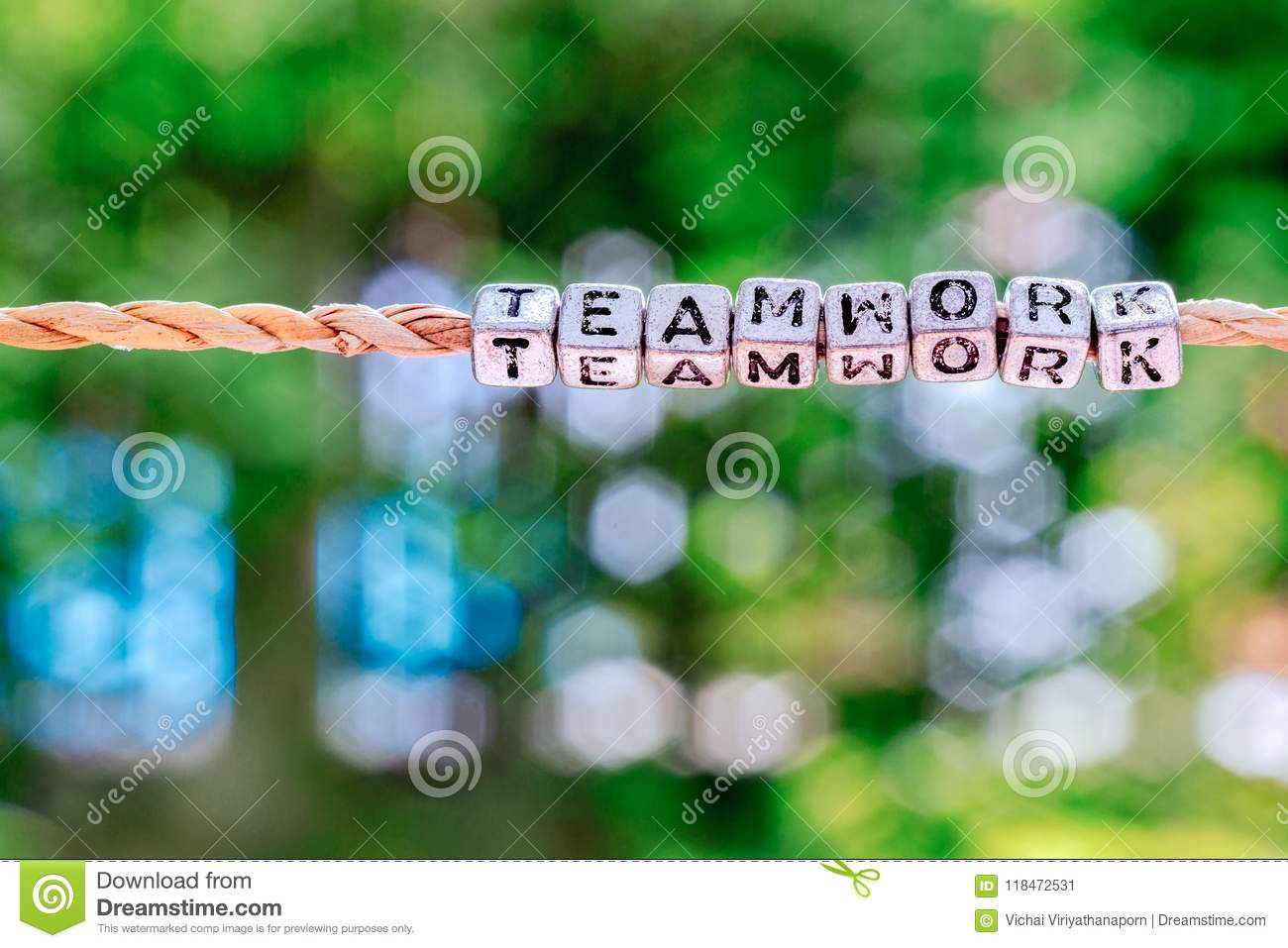 Teamwork word hanging by rope with beautiful green nature bokeh