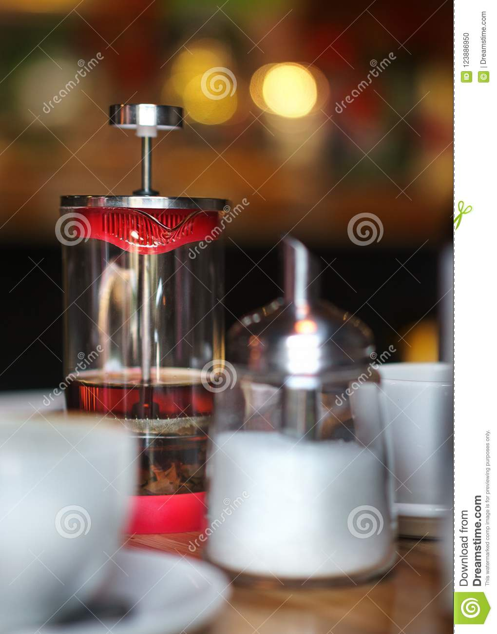 A teapot of green tea, a sugar bowl, cups are all in the foreground. On the back there is a mysterious bokeh. A cozy cafe, pleasan