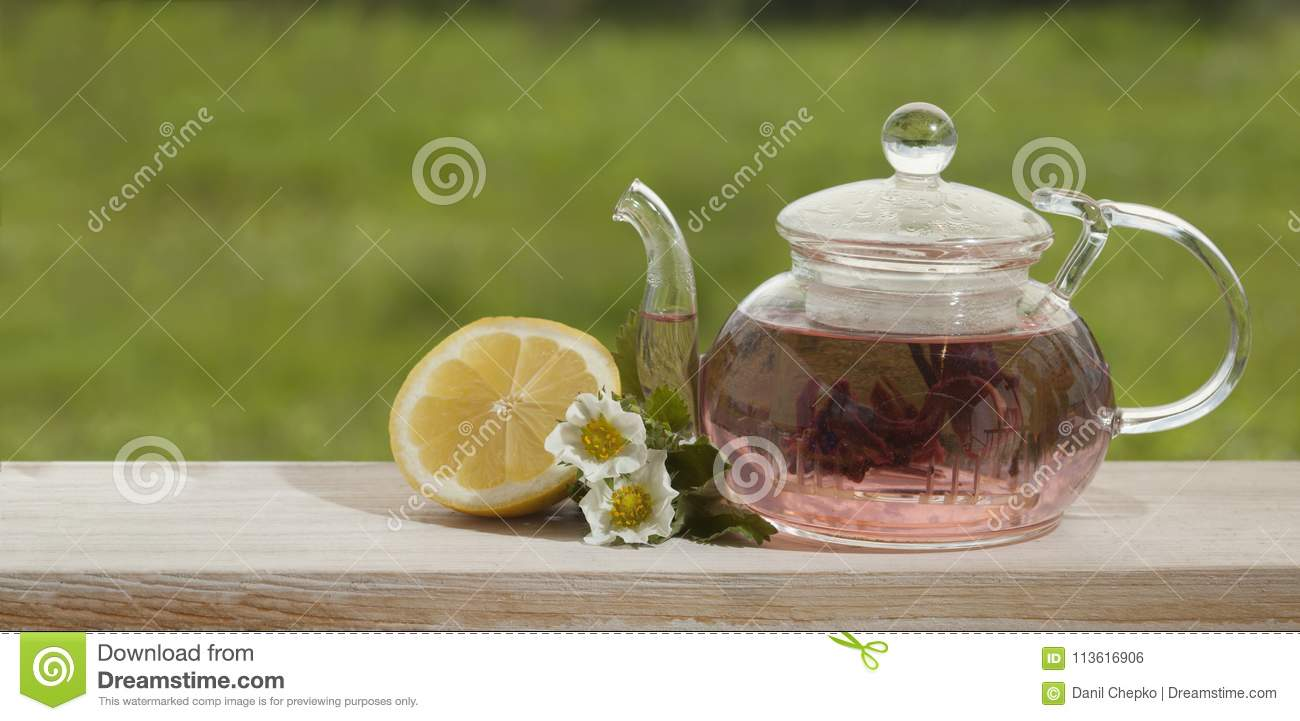 Teapot with lemon tea on a background of nature