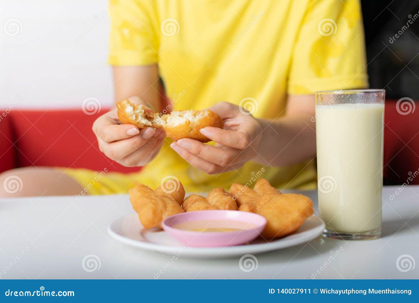 Tearing hand van vrouw braadde broodjes dichtbij het glas sojaboonmelk op de lijst