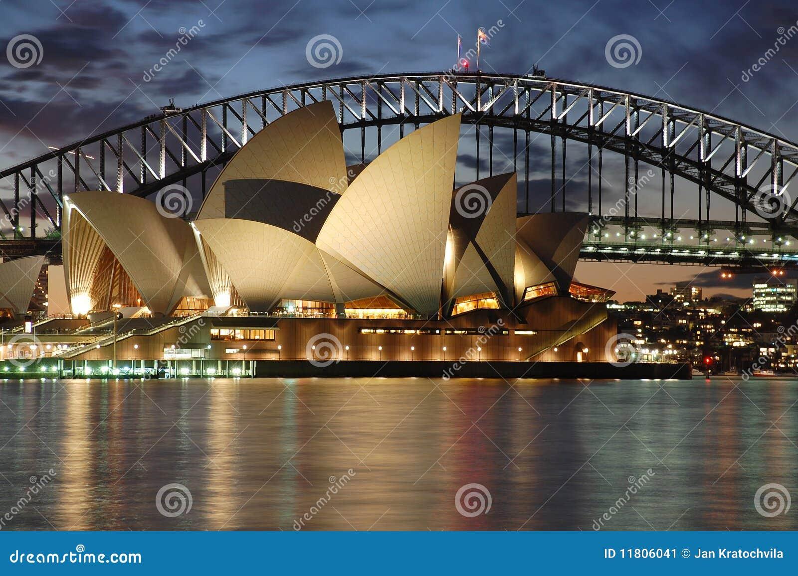 Teatro de la ópera de Sydney de la noche con el puente del puerto