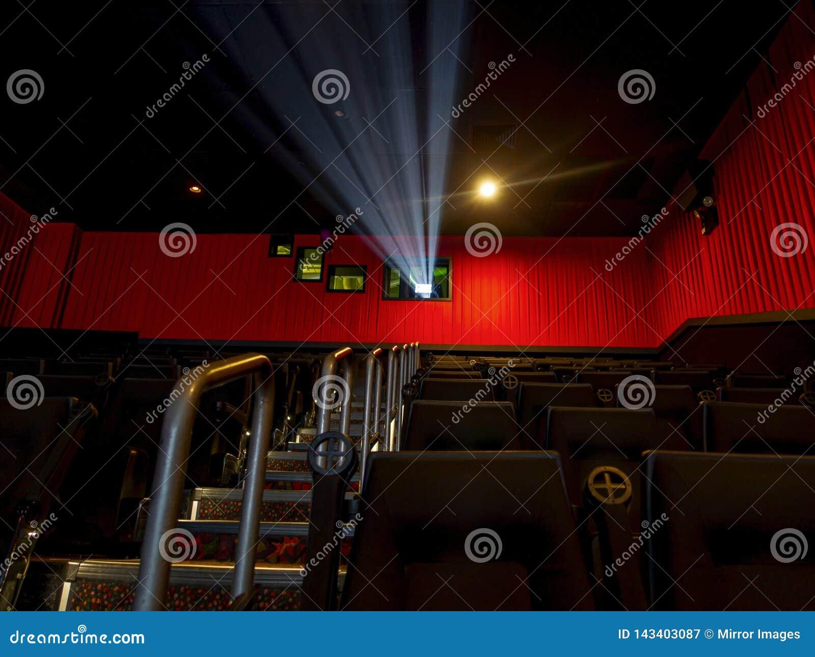 Teatro di schermatura d argento della stanza di film con la luce del proiettore su e disposizione dei posti a sedere e scale sull
