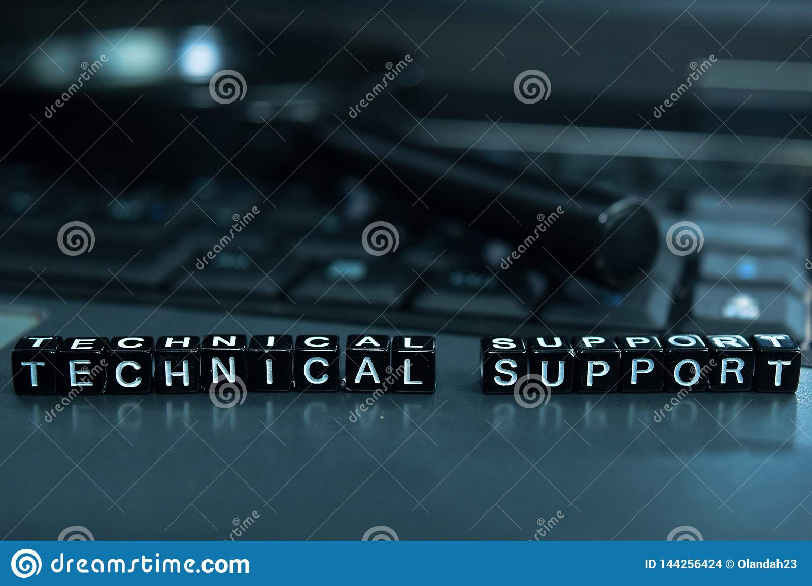 Technical Support text wooden blocks in laptop background. Business and technology concept