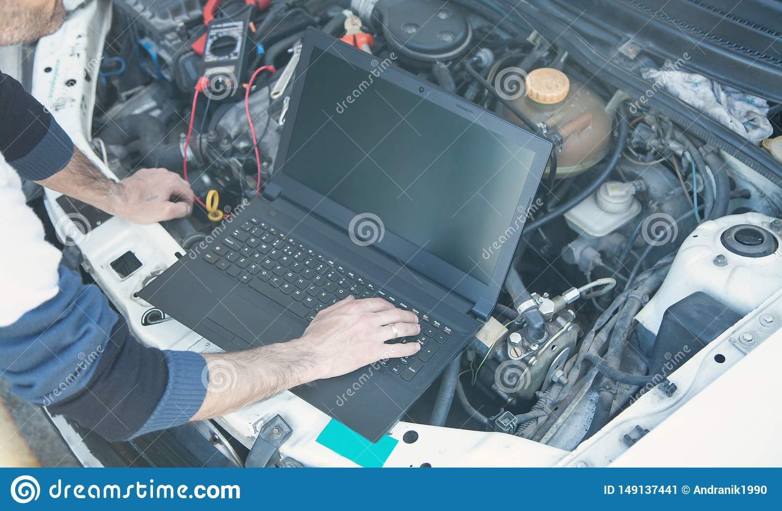 Technician checking car engine with a using laptop