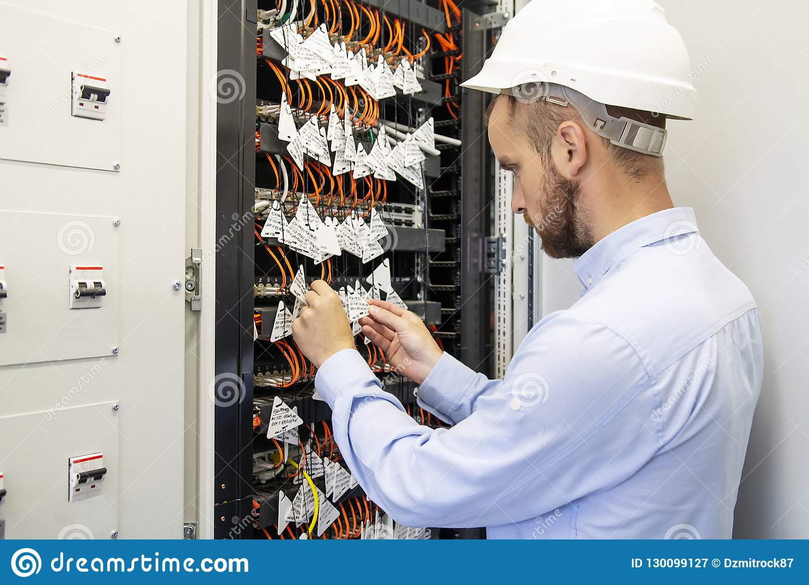 Technician engineer connects optical fibers into communication switch in data center. Service man in datacenter