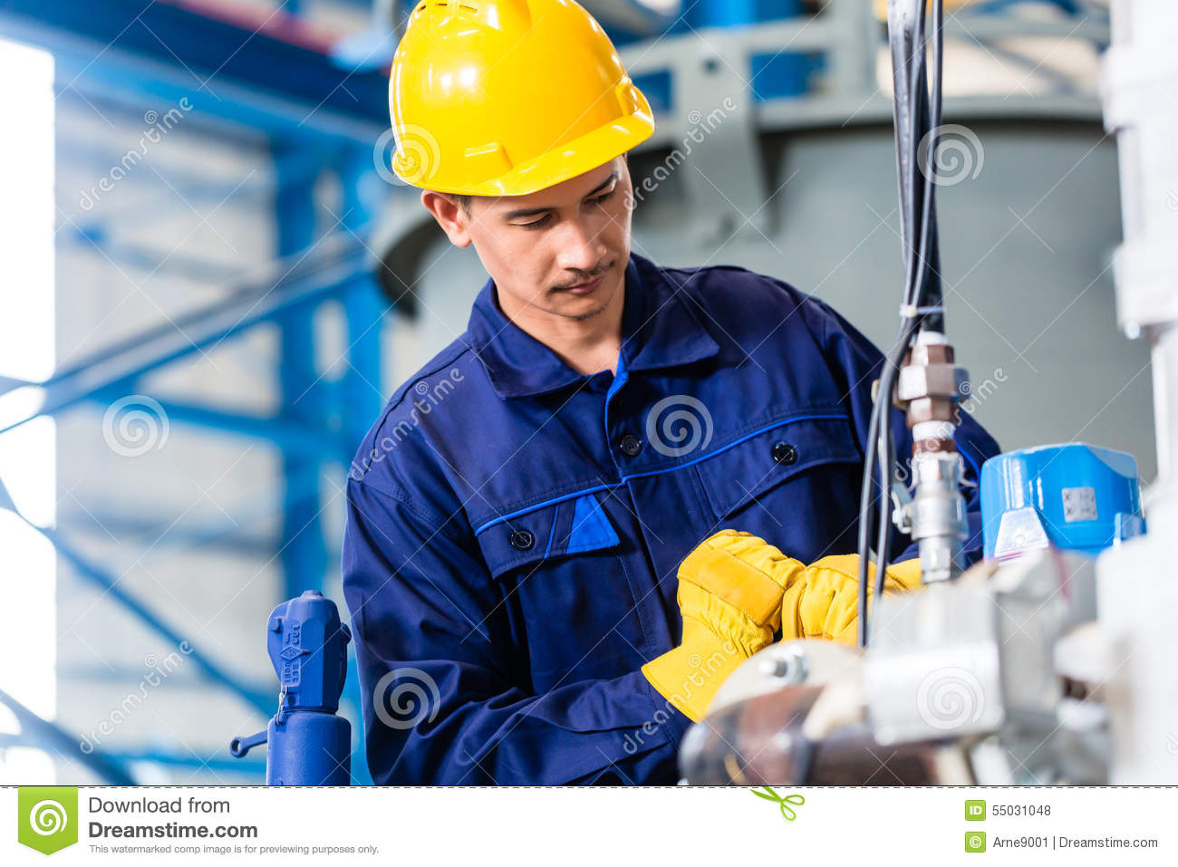 technician in factory at machine maintenance