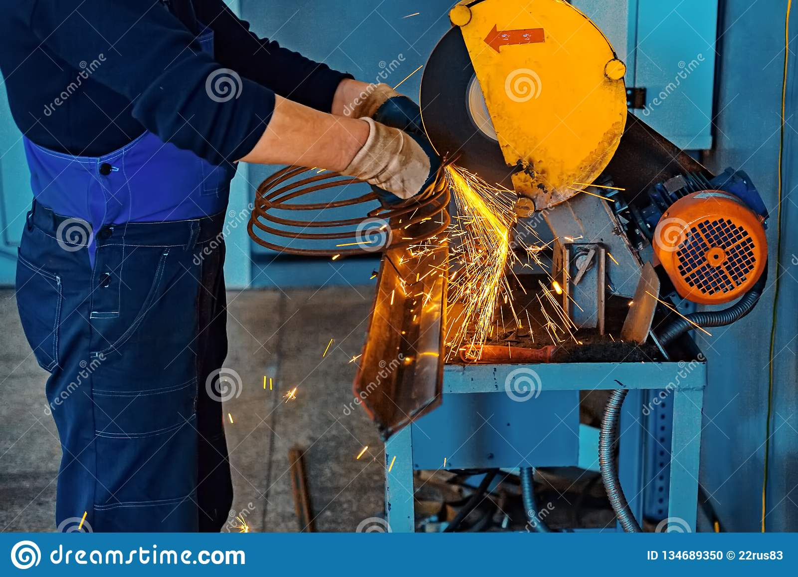 Technician in gloves and overalls in the workplace. Cutting metal with a machine in the shop