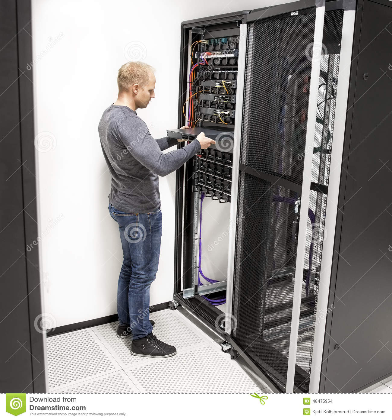 IT Technician Install Network Rack In Datacenter Stock Photo