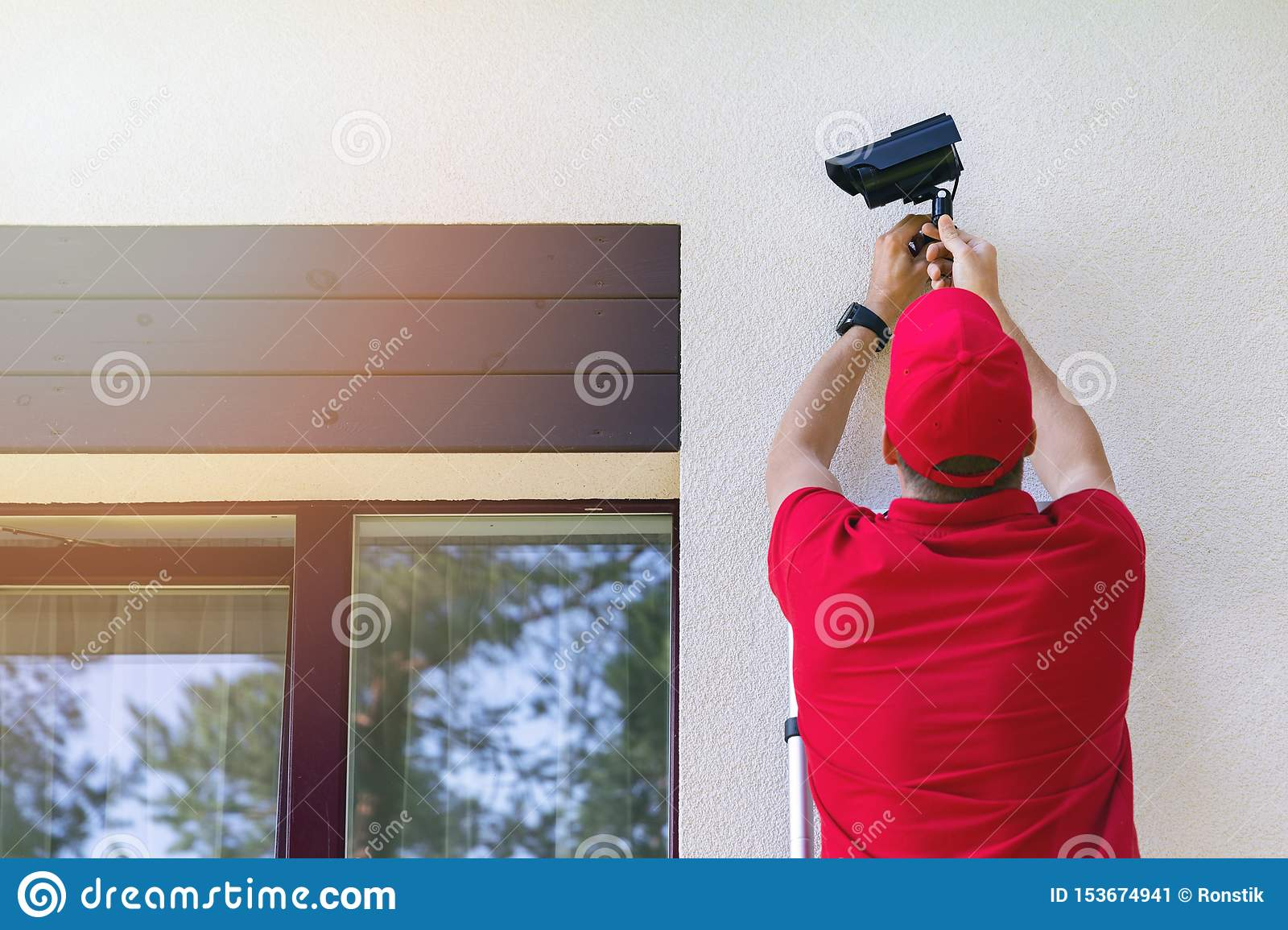 Technician installing outdoor security surveillance camera on house exterior wall