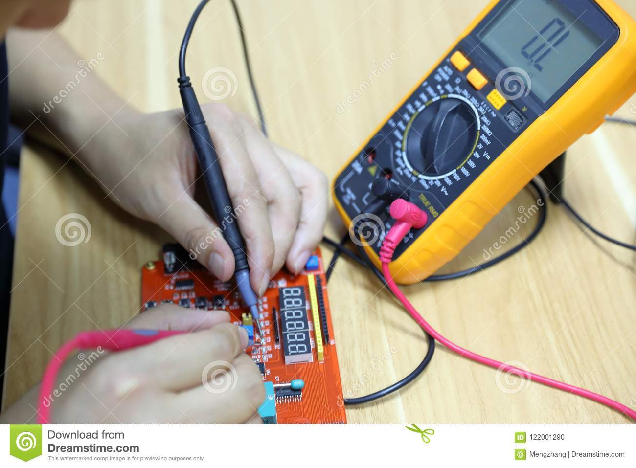 multimeter probes examining a computer circuit board stock phototechnician repairing computer hardware in the lab man use wiring diagram and multimeter
