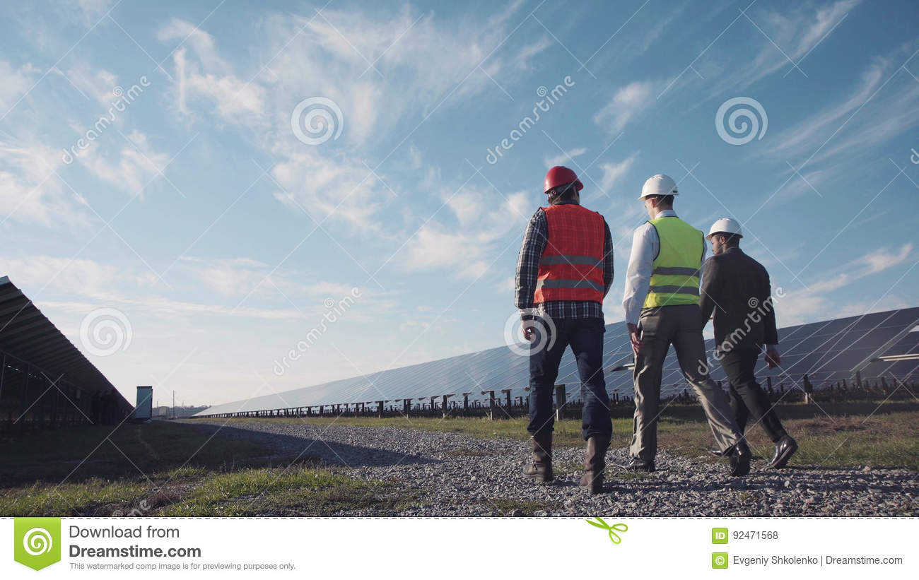 Technician walks with workman and investor