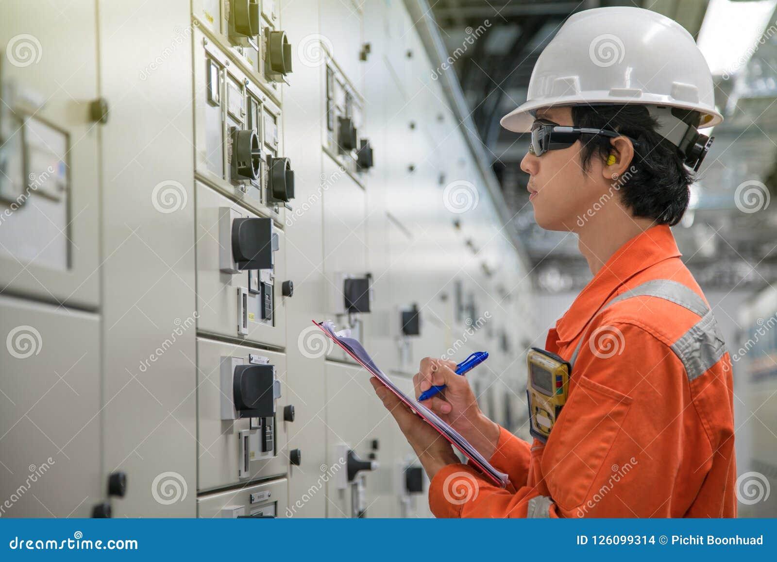 Technicien électrique et d instrument vérifiant les systèmes de contrôle électriques du processus de pétrole et de gaz