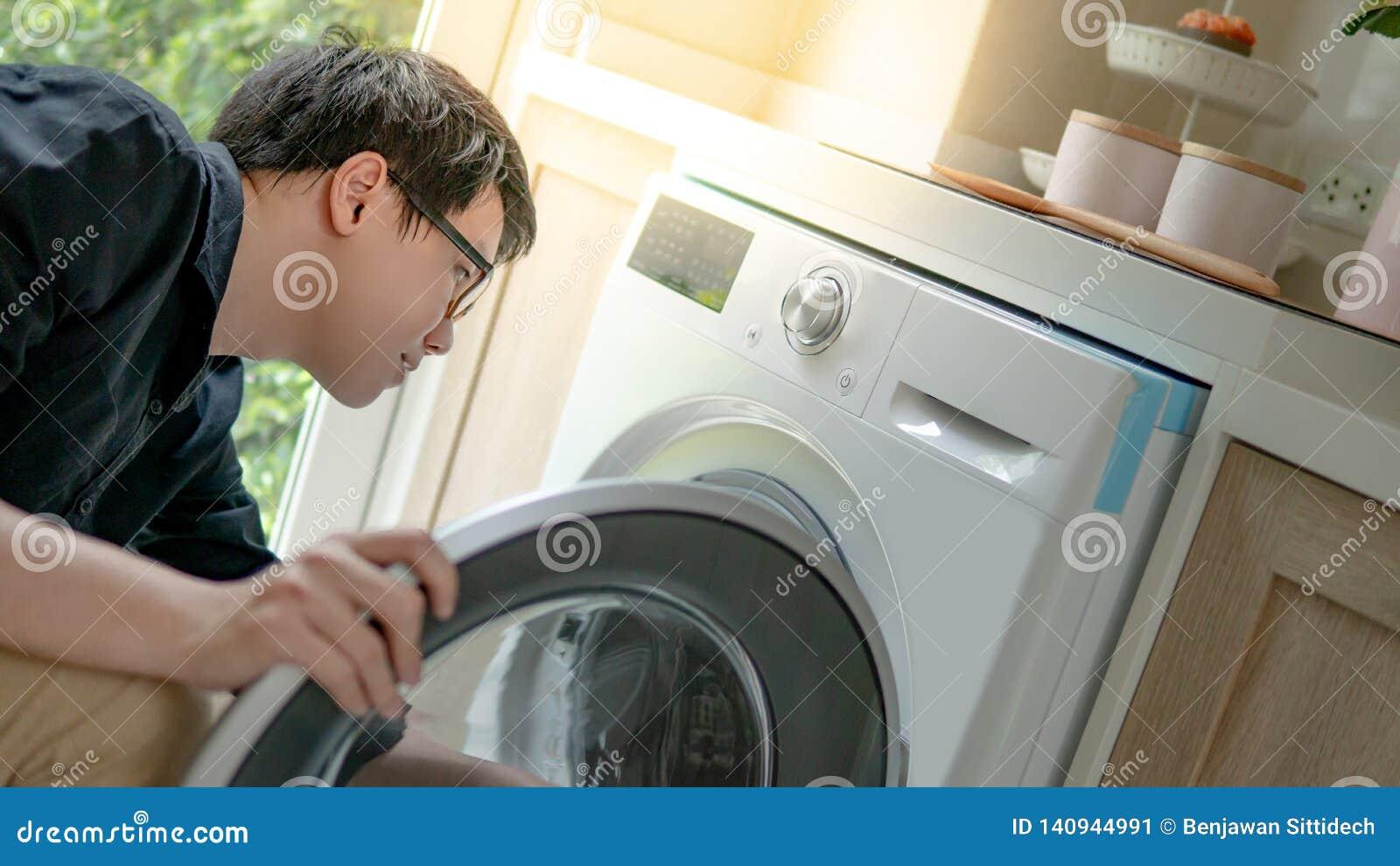 Entretien Machine A Laver technicien asiatique regardant dans la machine à laver image