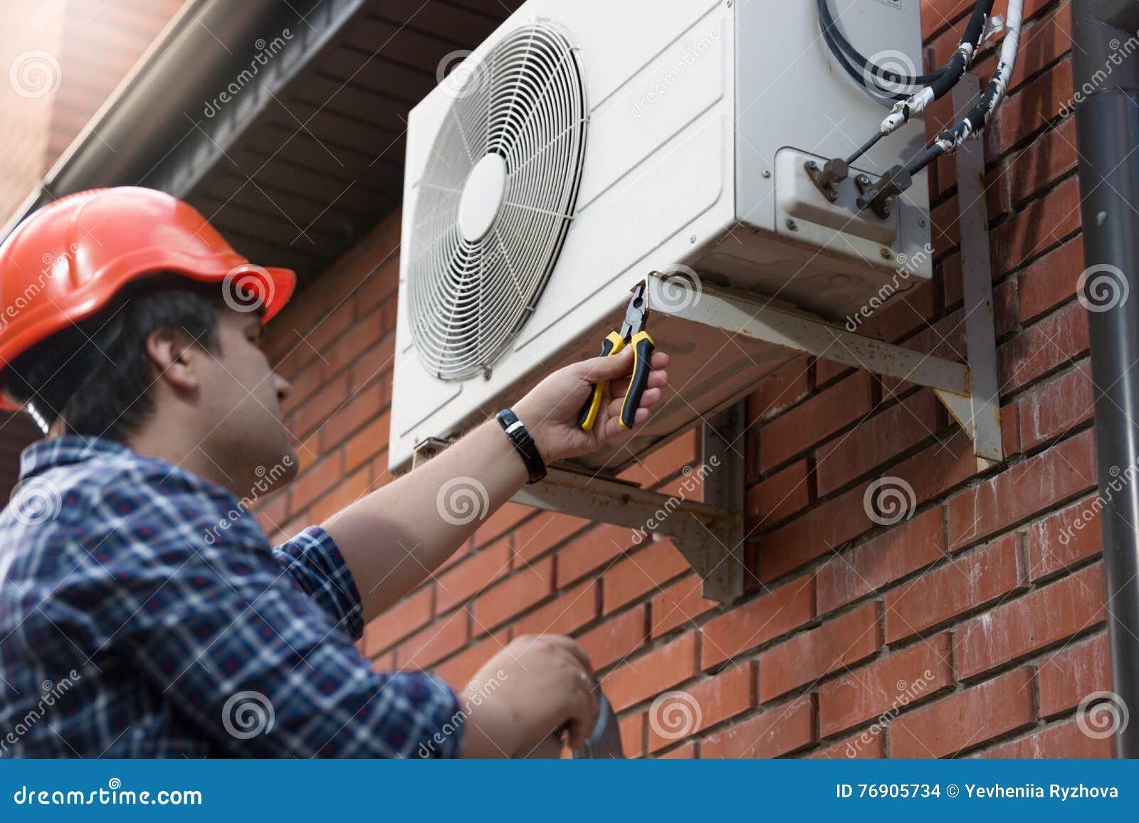 Technicien dans le masque reliant le dispositif climatique extérieur