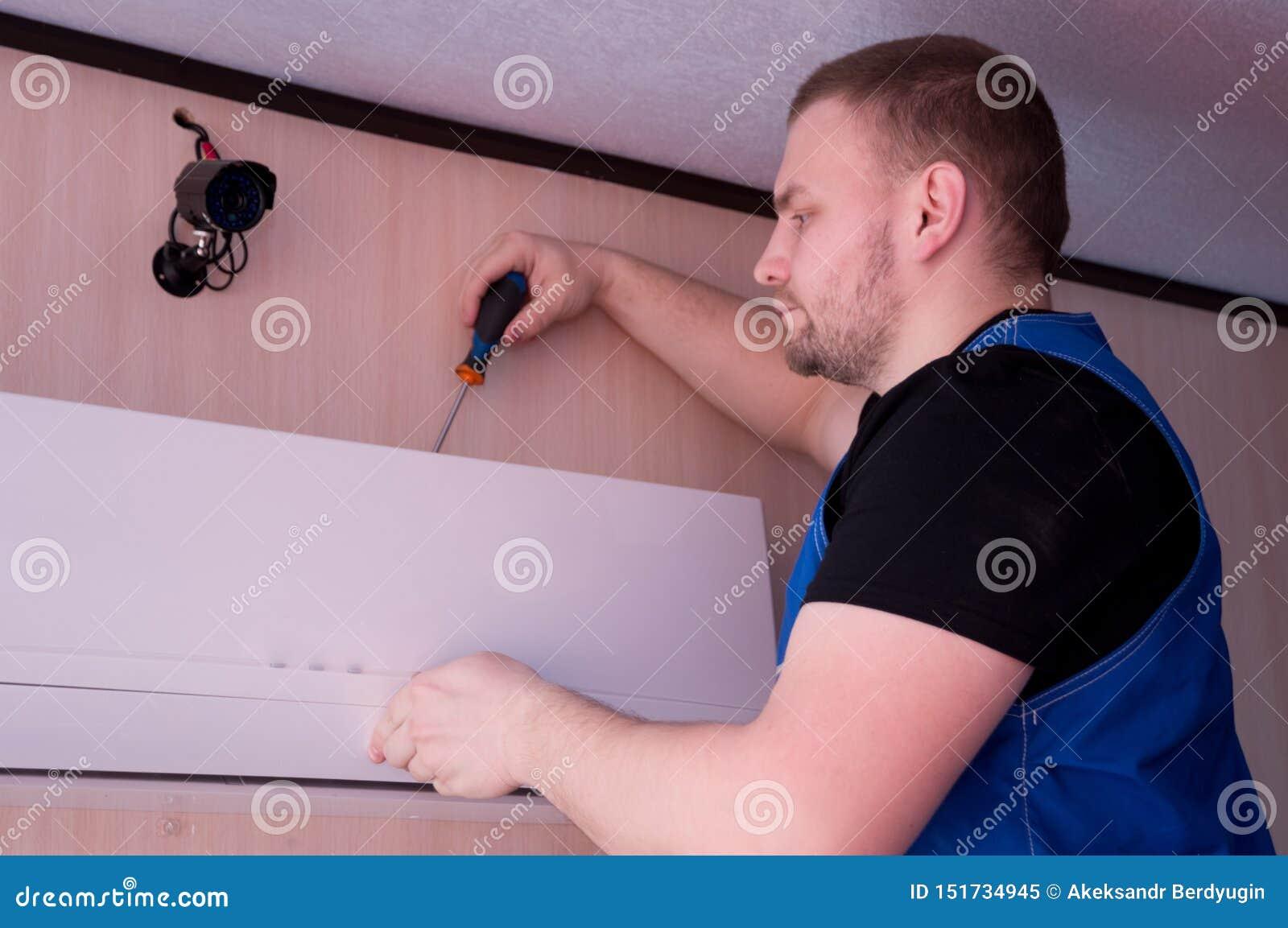 Technicien masculin r?parant le climatiseur ? l int?rieur