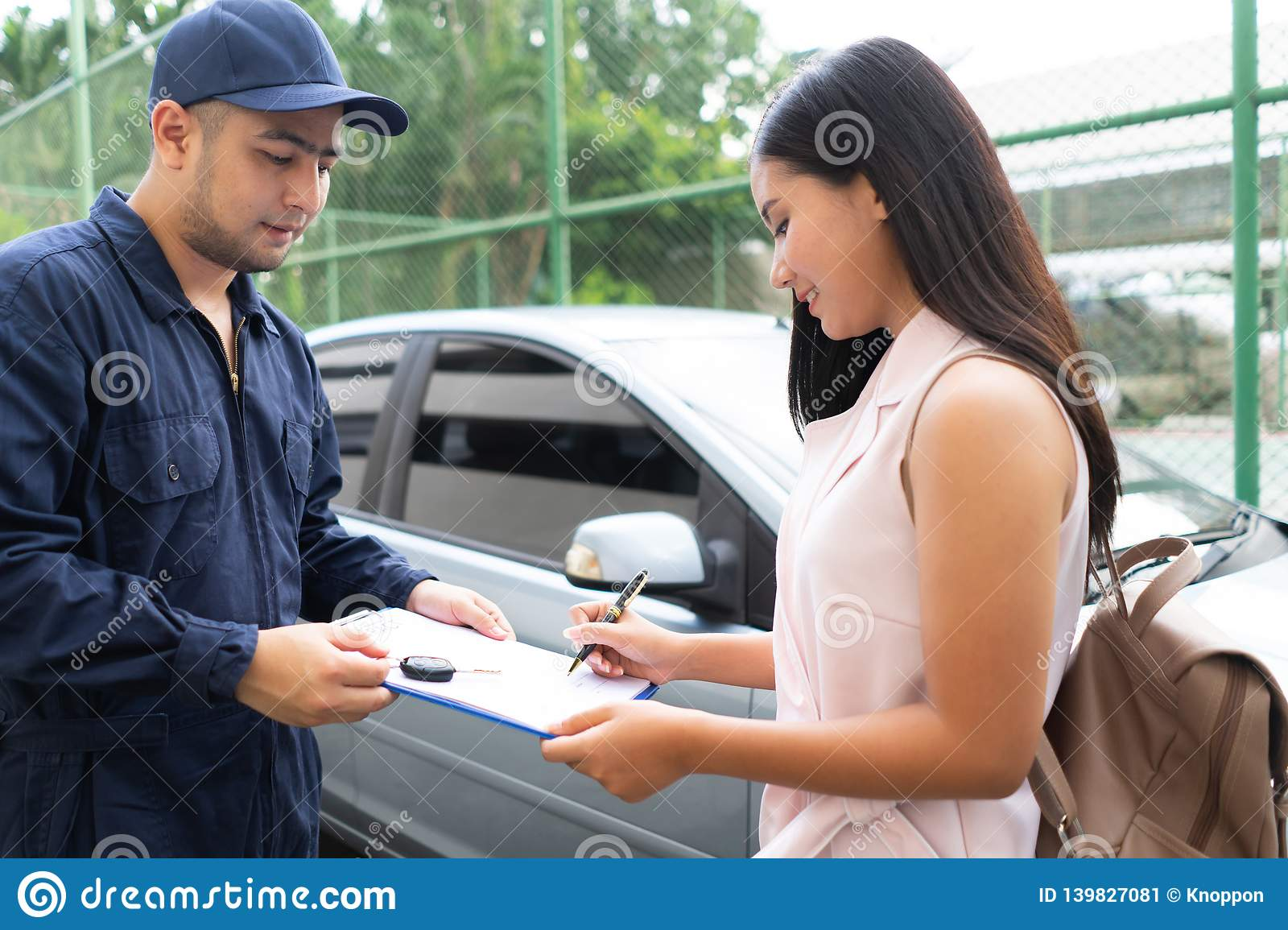 Technicisn repairman daje samochodu kluczowi kobieta w workshop Warsztatowy mechanik naprawy klienta samochód w samochód usługi