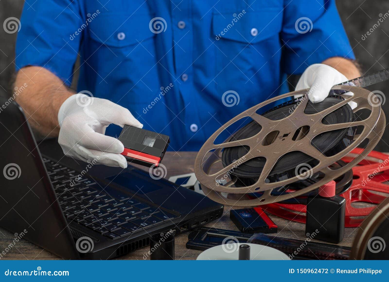 Technik z białymi rękawiczkami digitizing starego film 16mm i DV