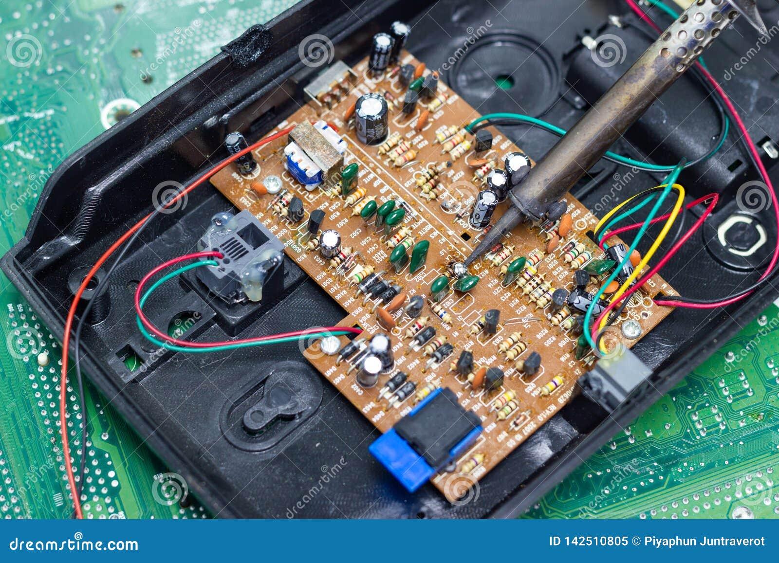 Technika naprawiać elektroniczny komputerowa ` s obwodu deska lutowniczymi żelazami