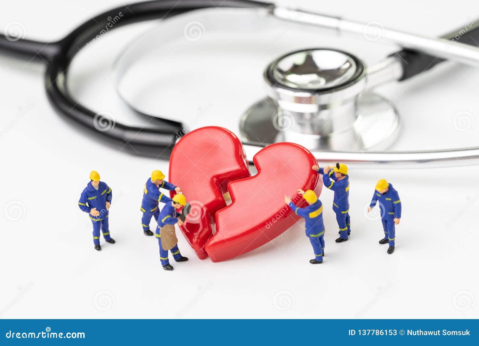 Techniker-Arbeitskraftteam der Miniaturleute nettes mit einheitlicher Hilfsfestlegung oder rotes defektes Herz mit Stethoskop auf