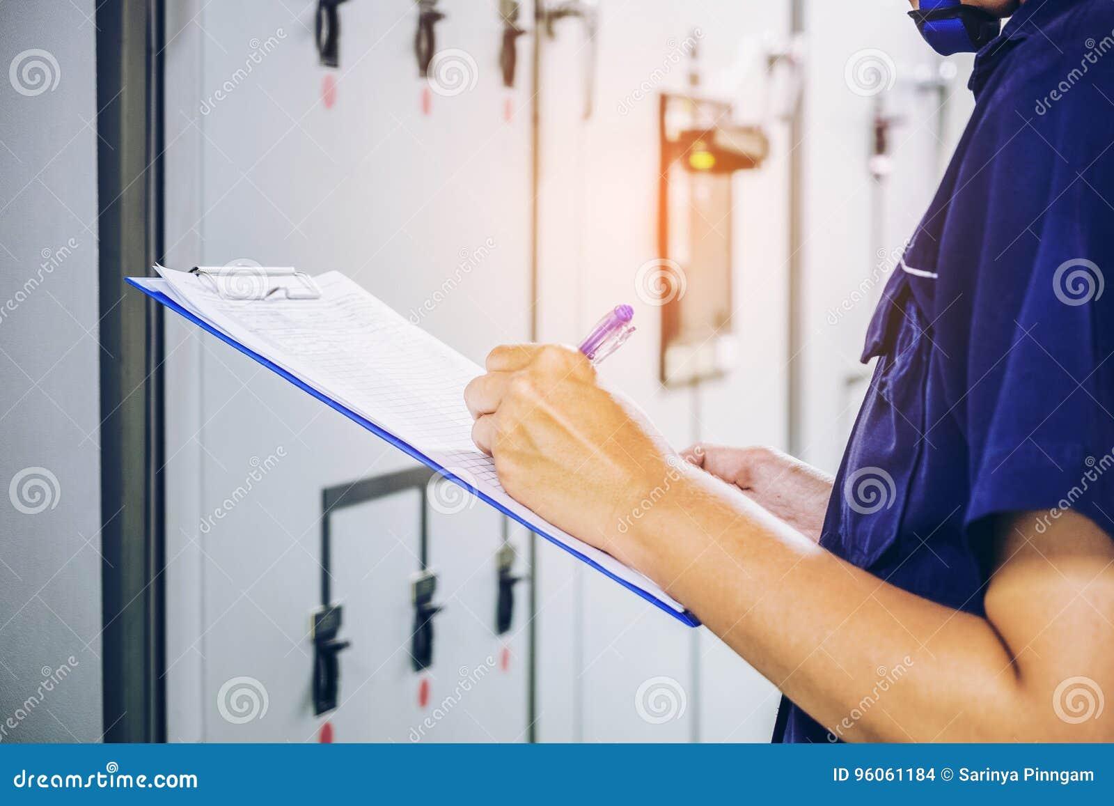 Techniker notiert Datenspannung oder -strom im Bedienfeld