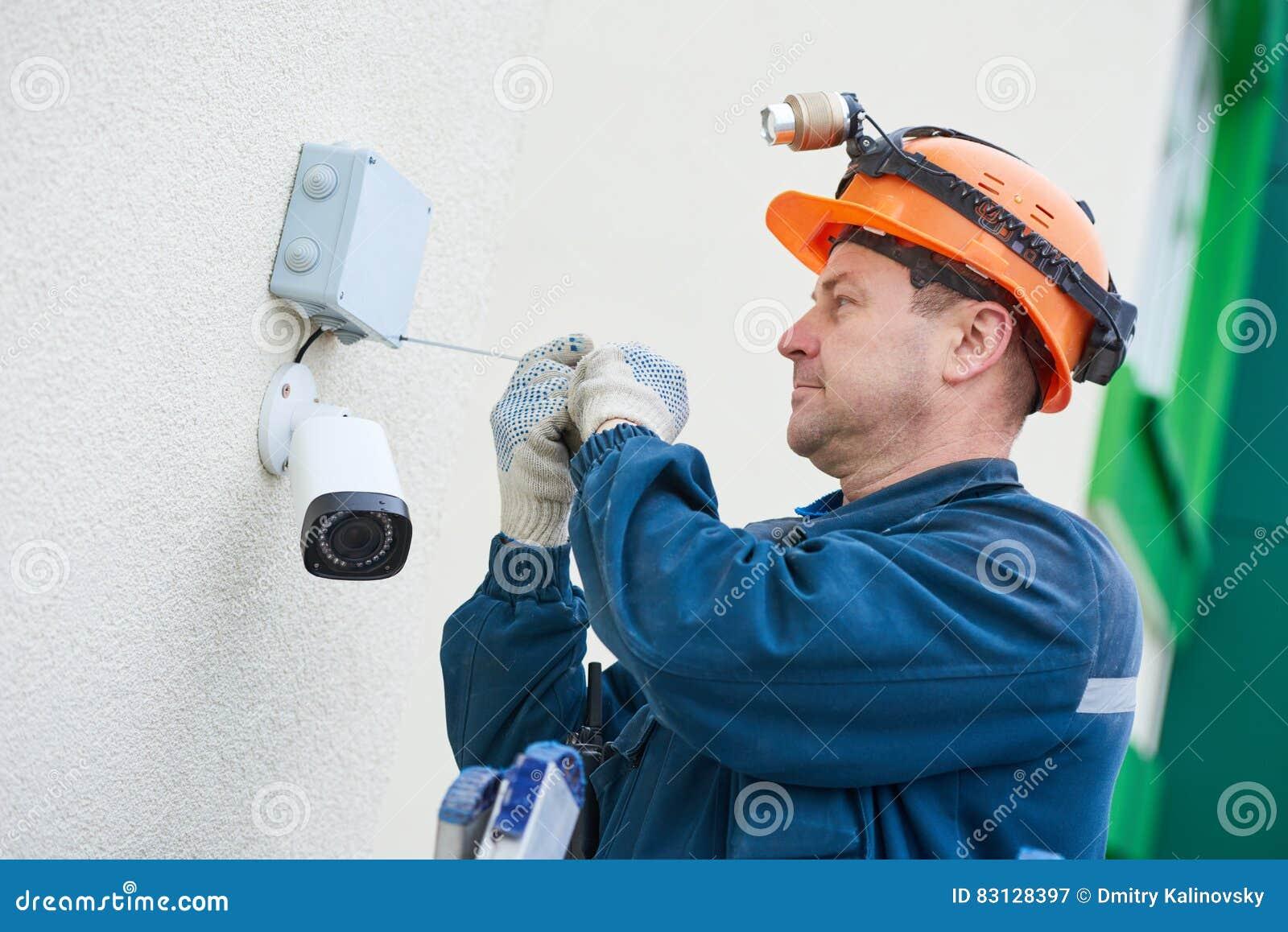 Technikerarbeitskraft, die Videoüberwachungskamera auf Wand installiert