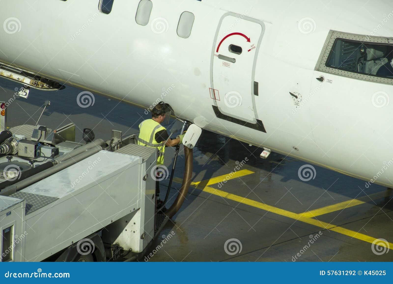 Technitian que trabalha abaixo de um avião do passageiro