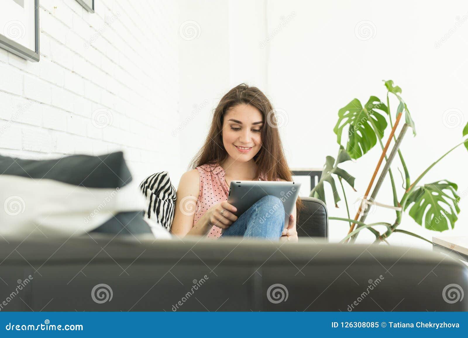Technologieën, mededeling, mensenconcept - de jonge vrouw zit bij bank en het babbelen in tablet en het glimlachen
