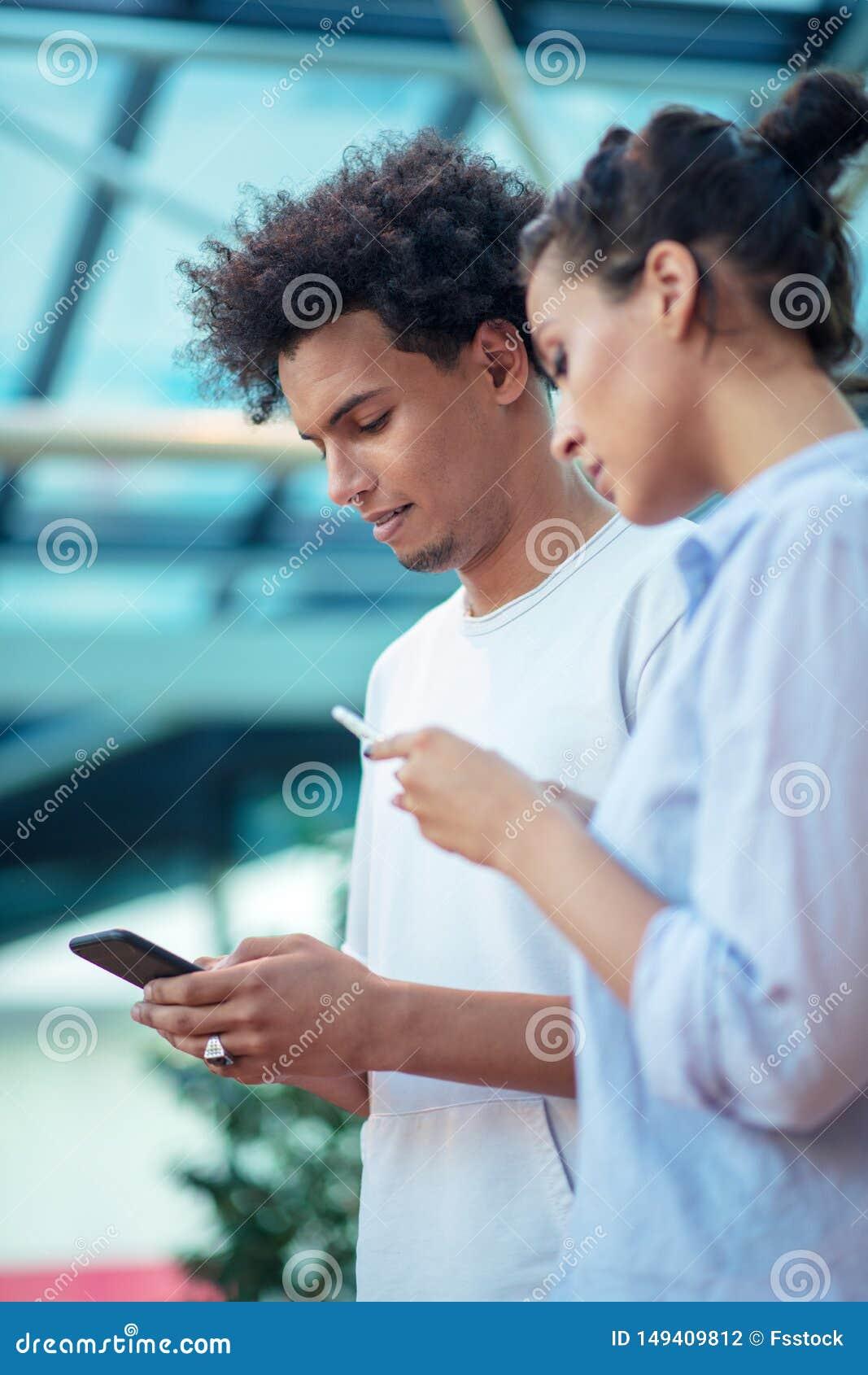 Technologie num?rique et d?placement Jeunes couples affectueux dans la tenue de d?tente utilisant le smartphone tout en se tenant