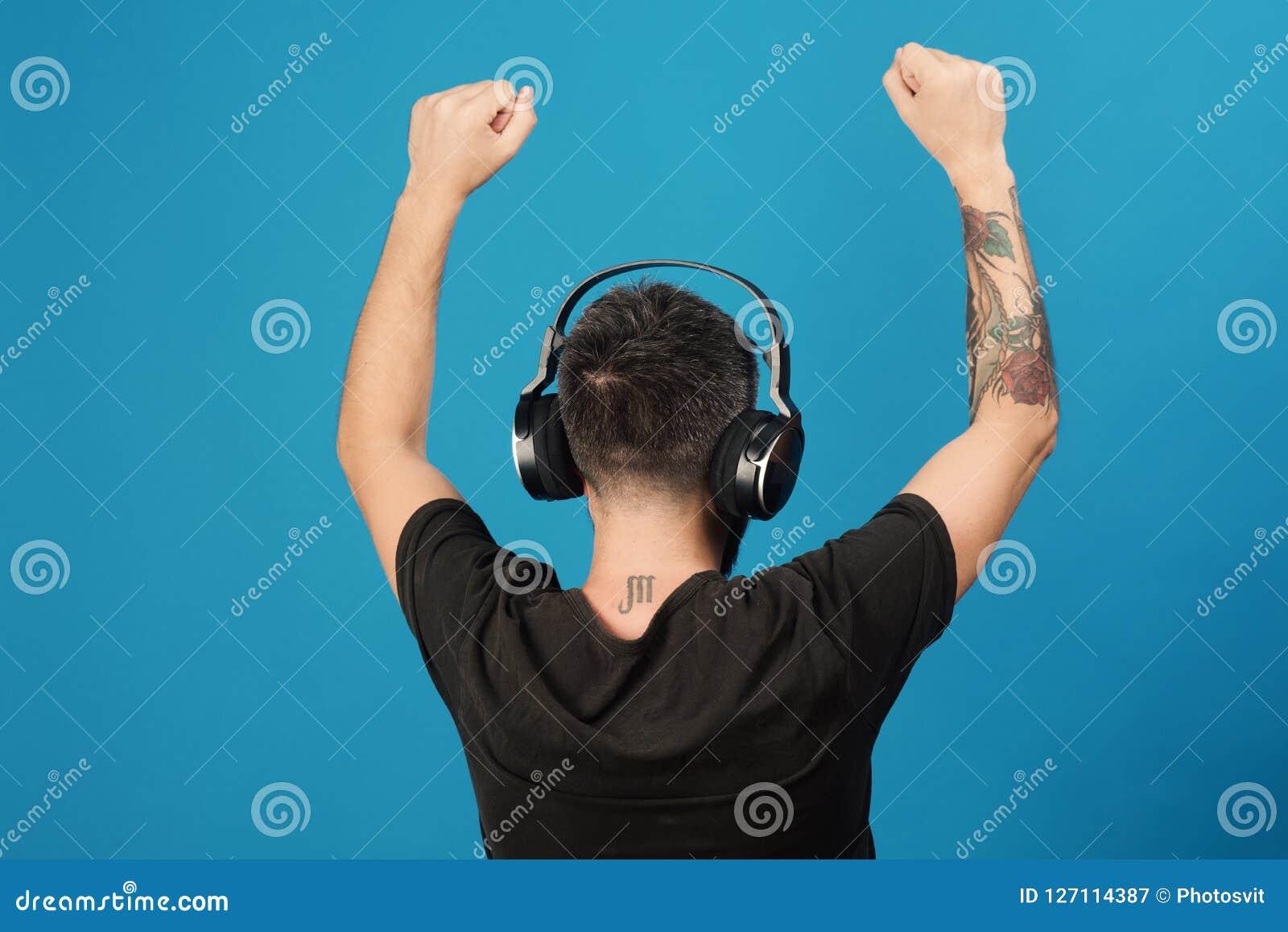 Technologies and music concept. Dj with scorpio tattoo wears headphones