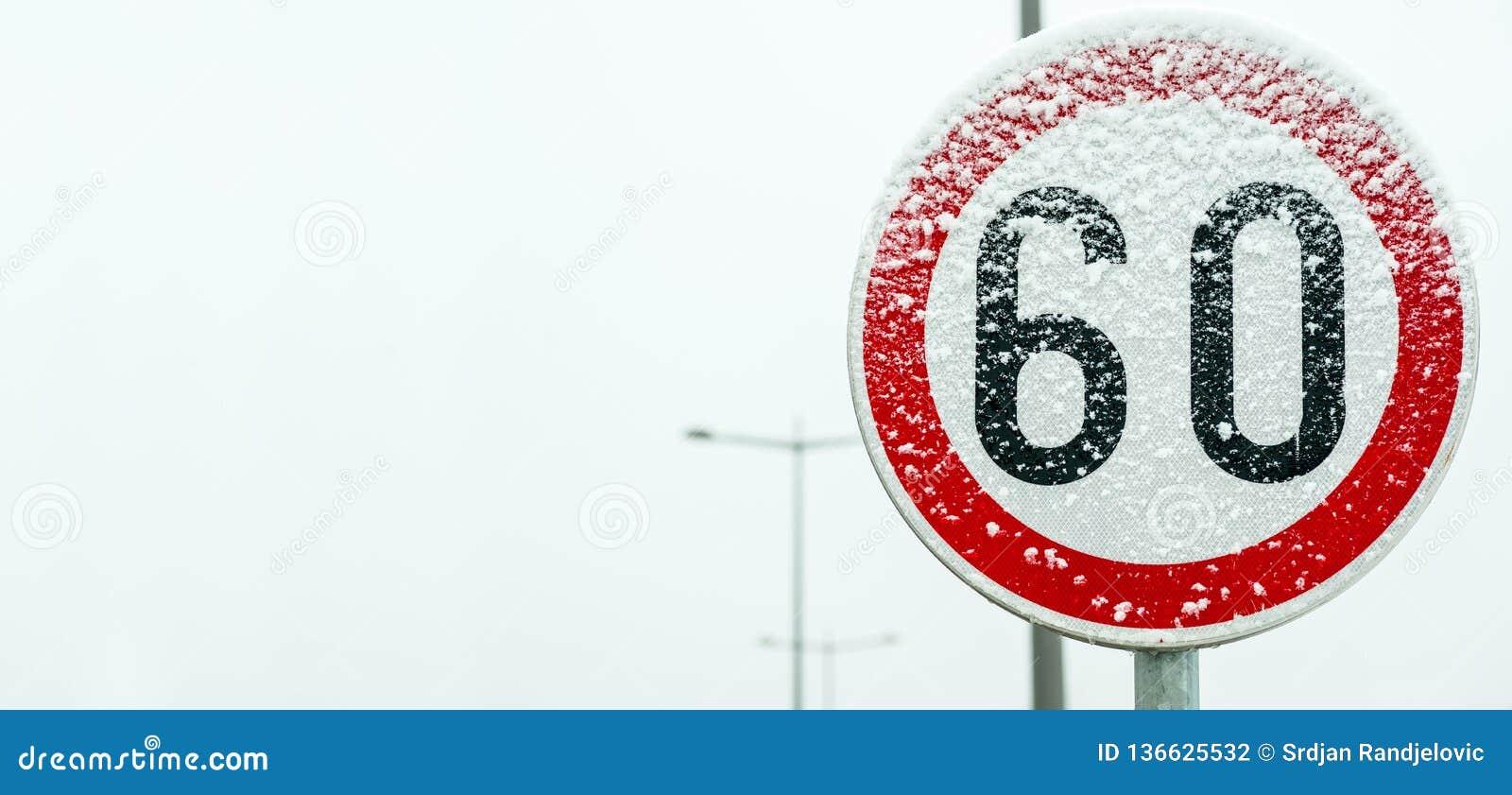 Tecken för trafikväghastighetsbegränsning 60 på gatan som täckas med för vintersäsong för insnöad fara halt slut upp med utrymme