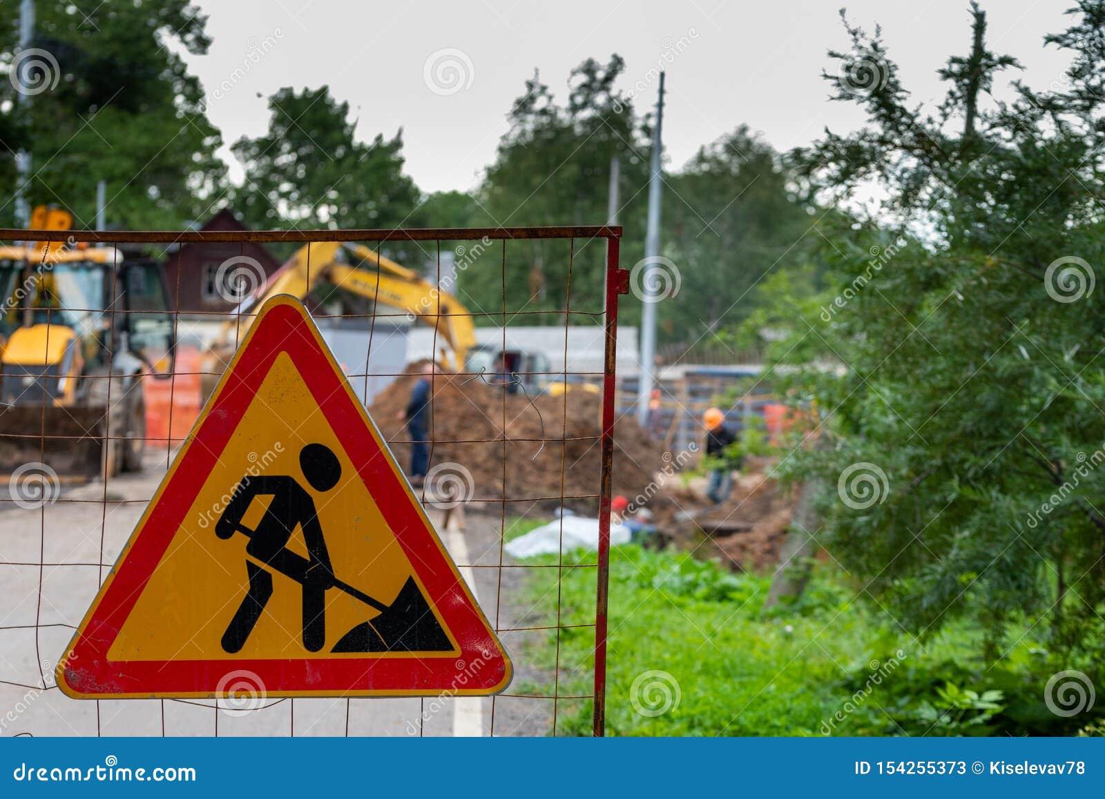 Tecken för vägarbeten på defocused bakgrund av arbetare och konstruktionsutrustning