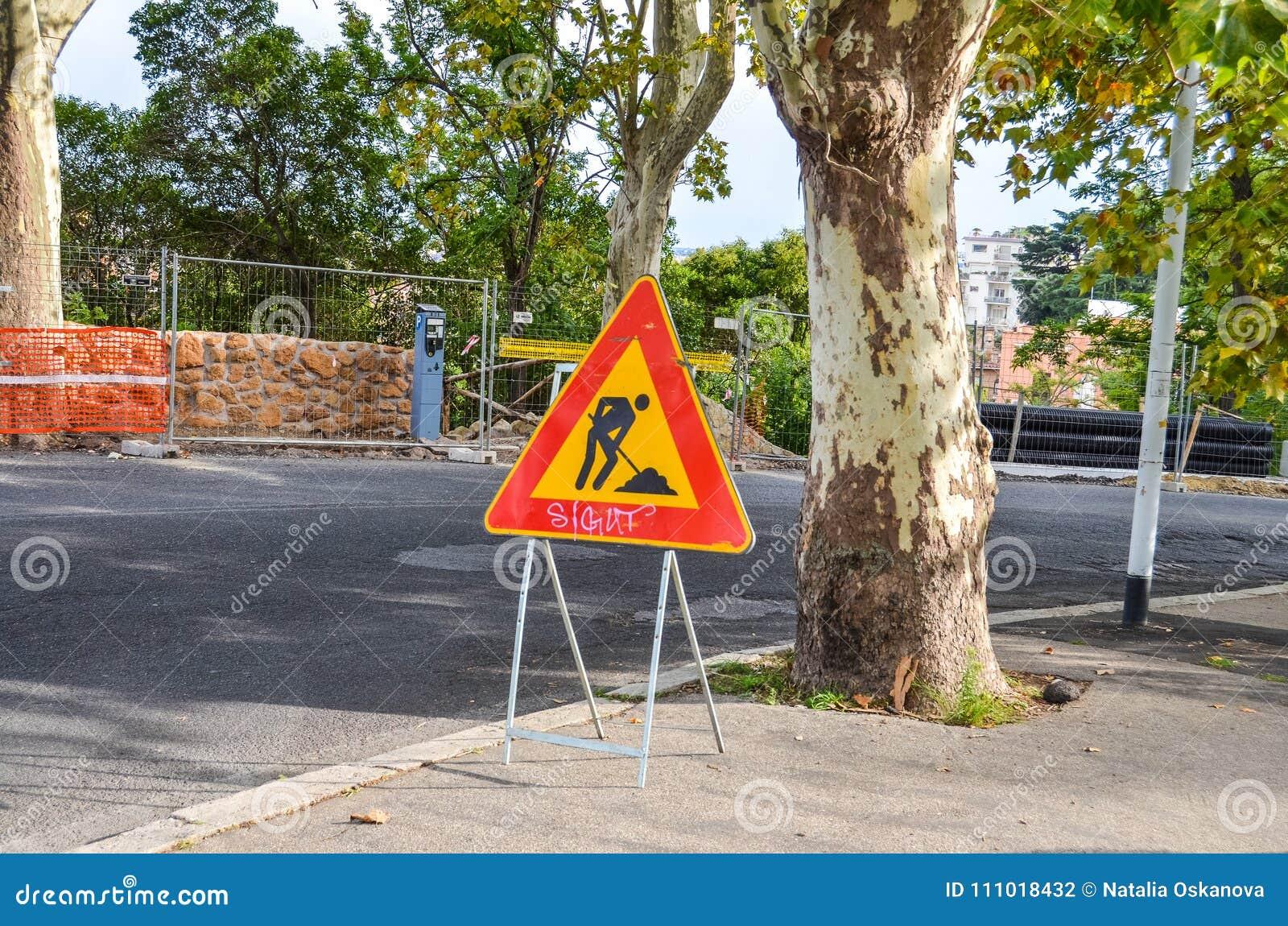 Tecken för vägarbeten på den soliga gatan