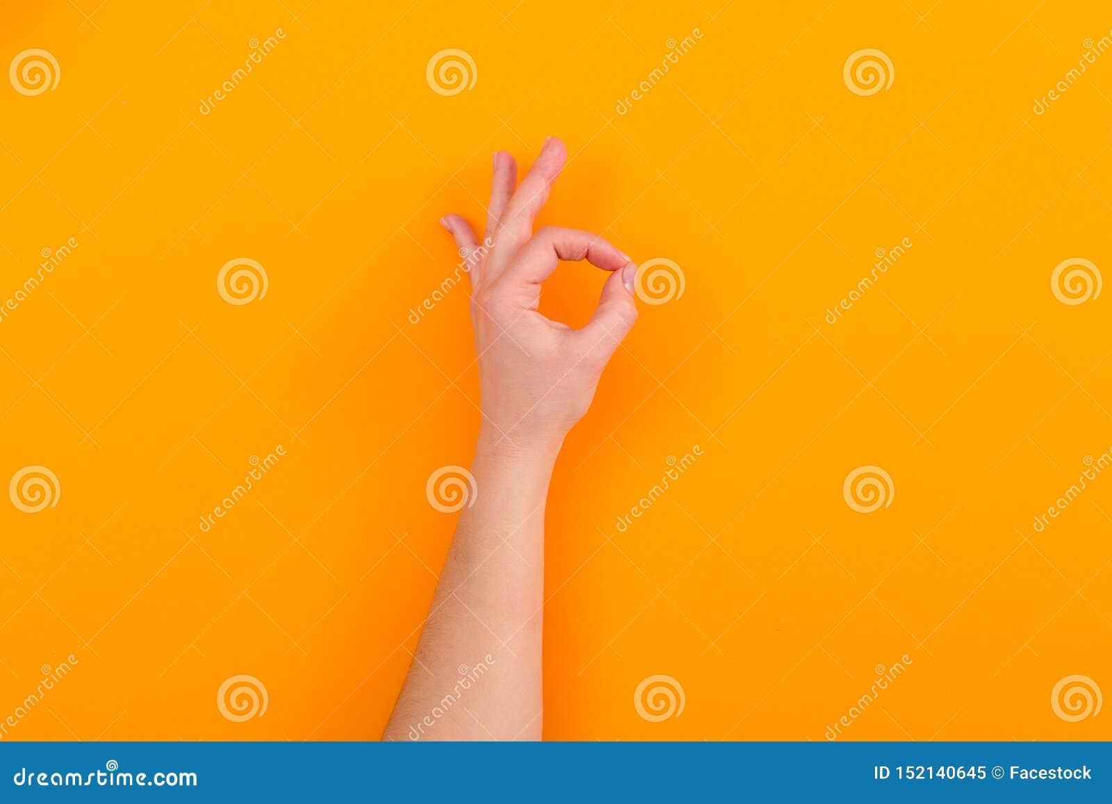 Tecken för visning för ung kvinna reko på orange bakgrund