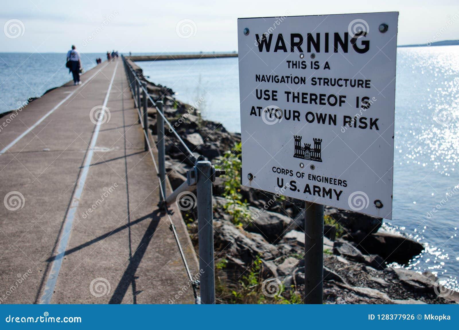 Tecknet varnar turister att vara försiktiga, när det går på vågbrytaren till vågbrytarefyren för två hamnar