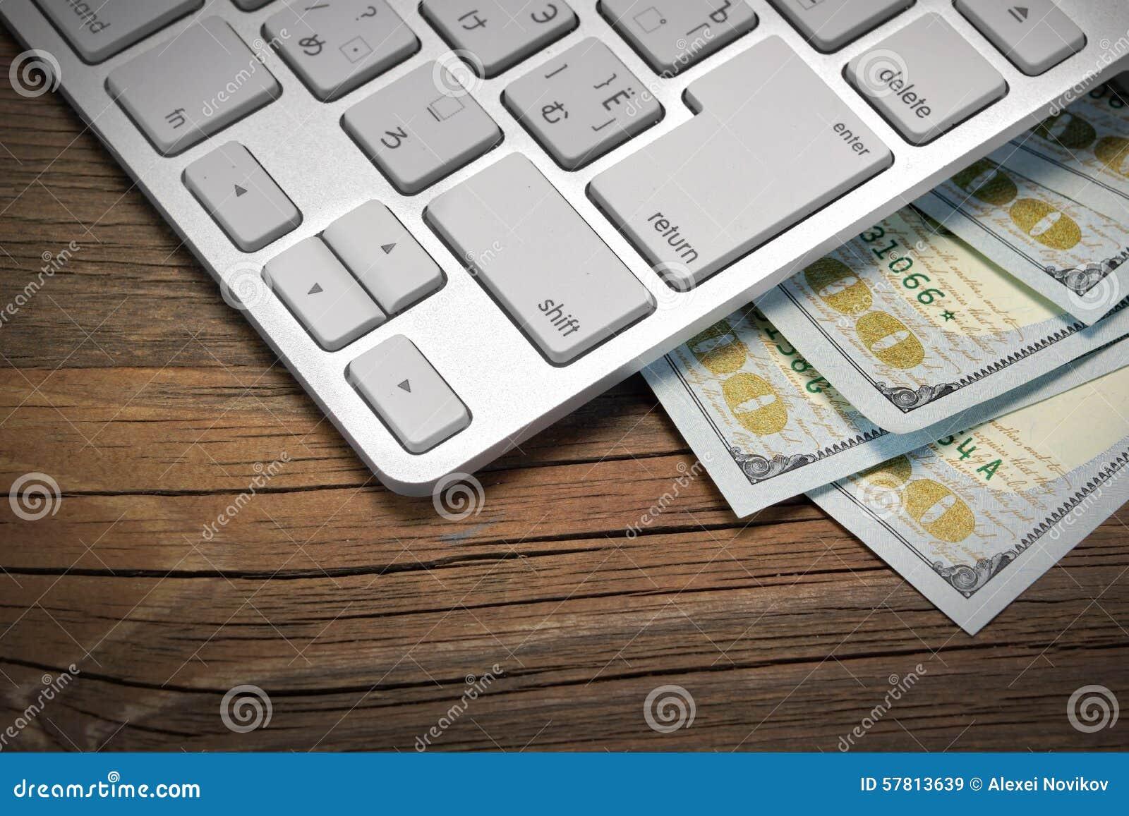 Teclado de ordenador y efectivo del dólar en el fondo de madera