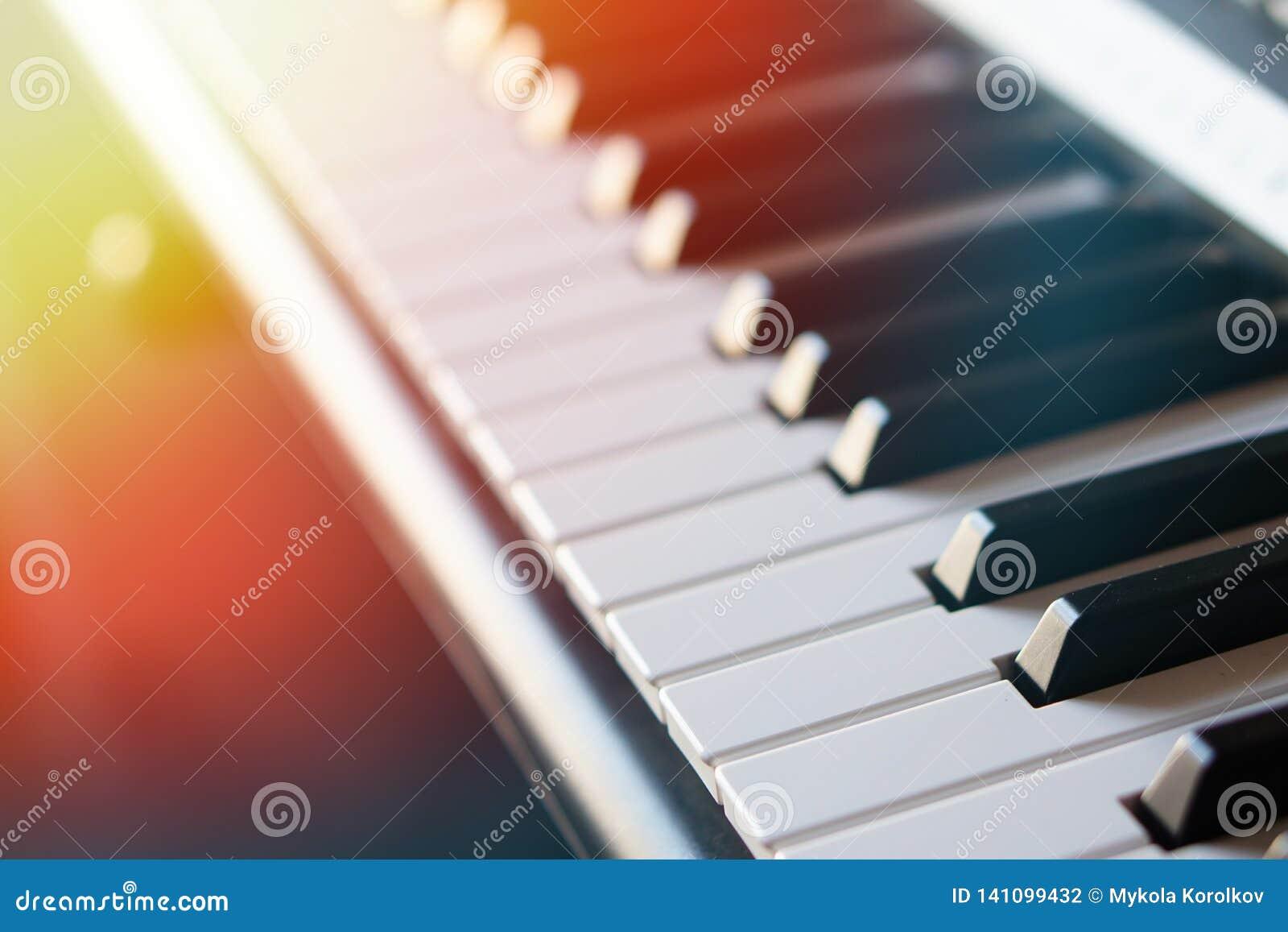 Teclado de piano electrónico del sintetizador en la macro de los rayos del sol
