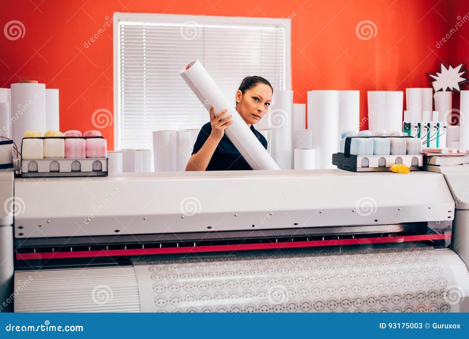 Tecnico che lavora alla macchina della taglierina e del tracciatore nella stampa del cen