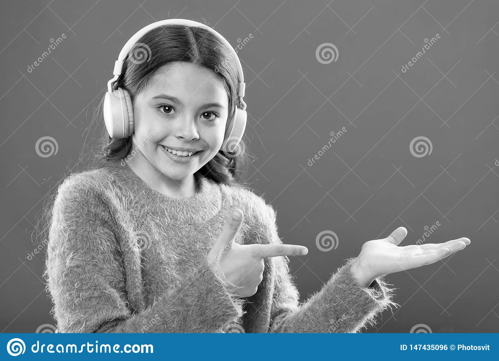 Tecnolog?a moderna inal?mbrica de los auriculares El ni?o de la muchacha escucha los auriculares inal?mbricos de la m?sica que se