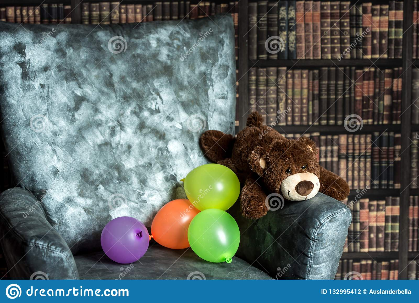 Plush Teddy Bear On The Armchair In The Room With Books Stock