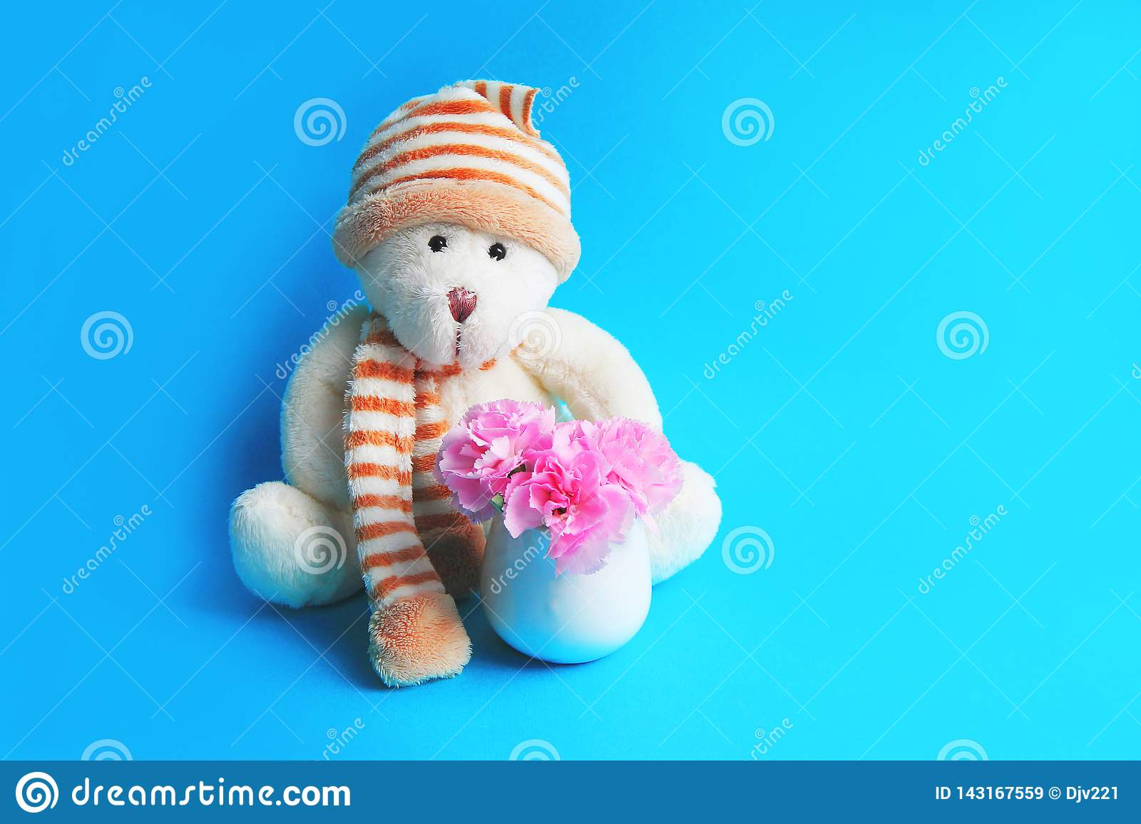 Teddy bear in a hat and balls next to a bouquet of pink carnations